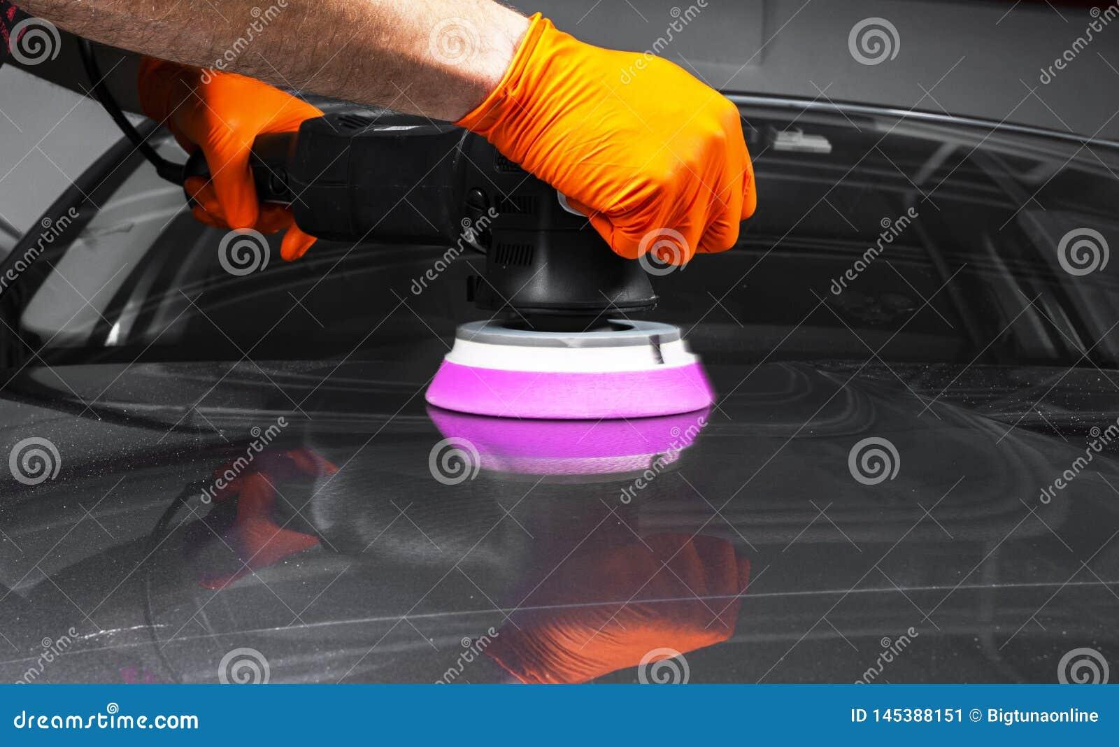 Mains polonaises de travailleur de cire de voiture appliquant la bande protectrice avant le polissage Voiture de polissage et de