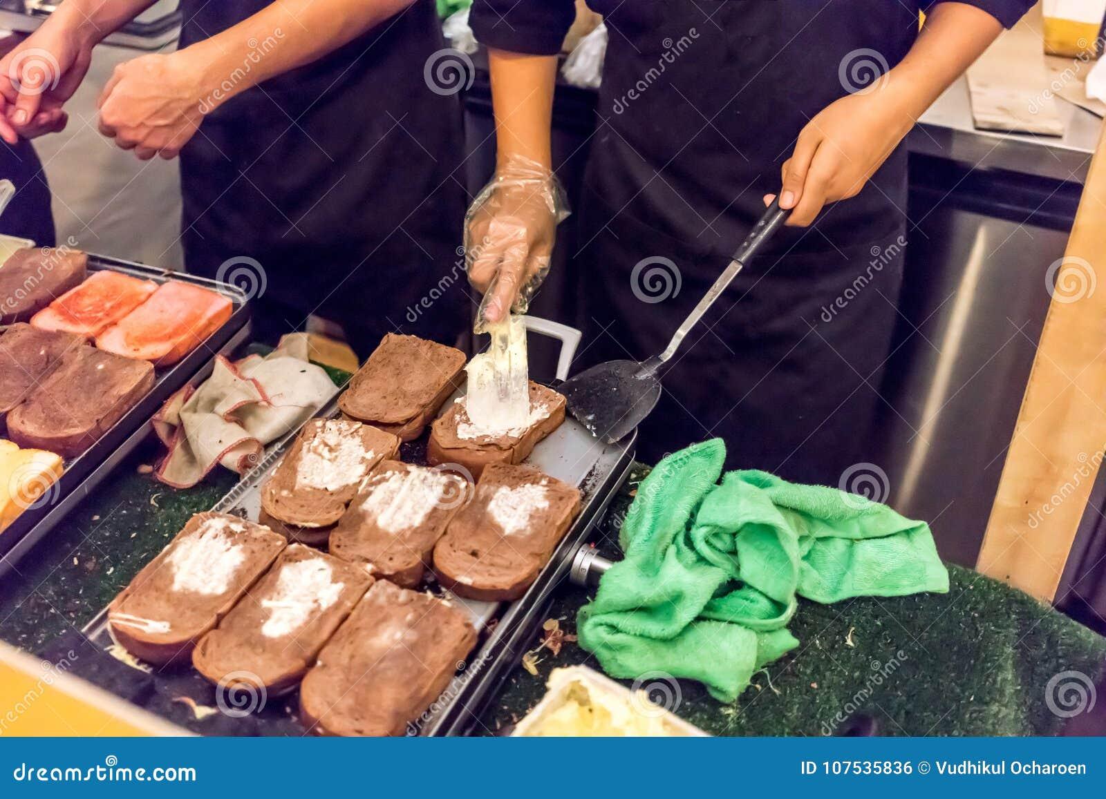 Mains répandant le beurre sur la variété de tranche fraîchement grillée de pain