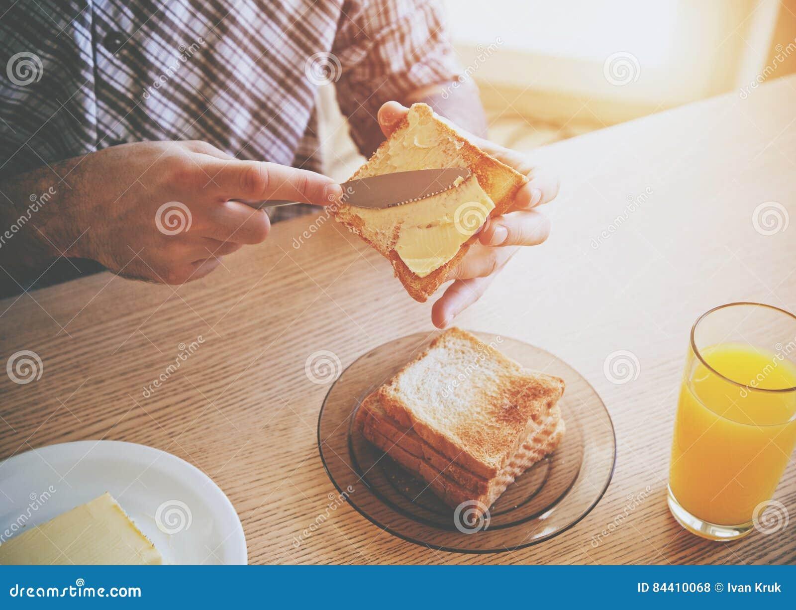 Mains répandant le beurre sur le pain grillé