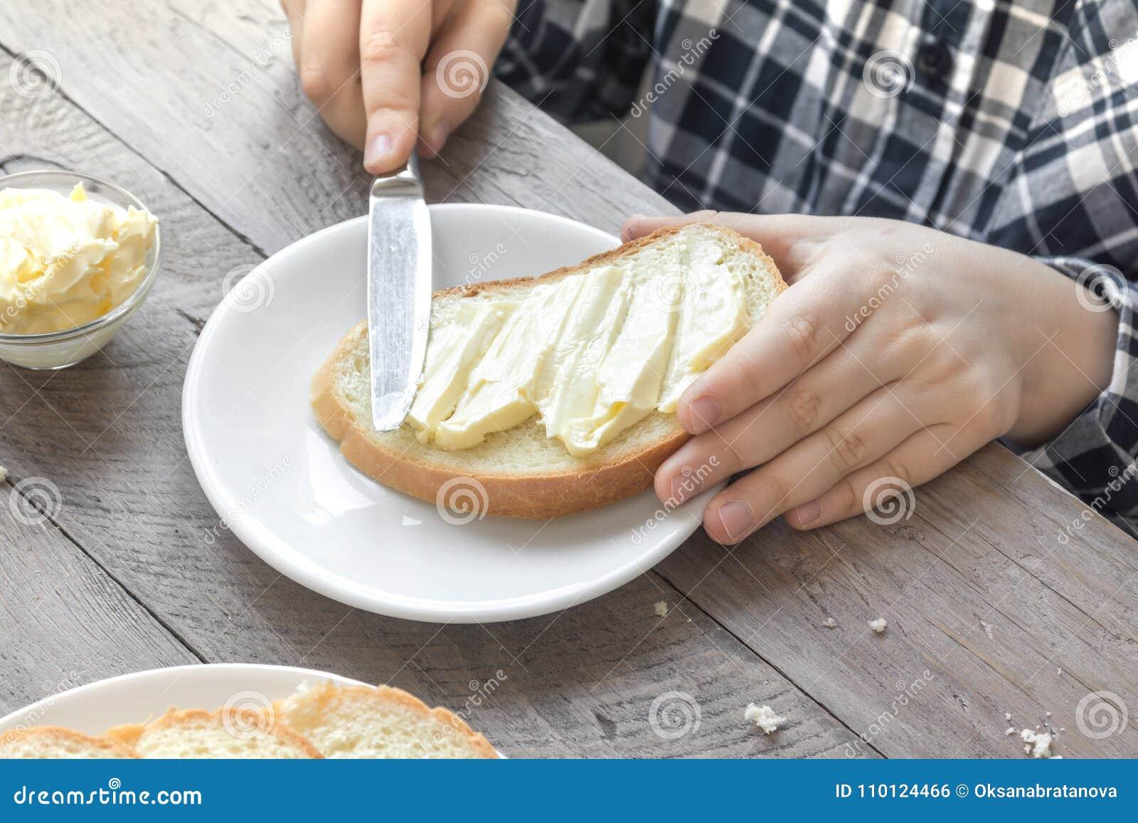 Mains répandant le beurre sur le pain
