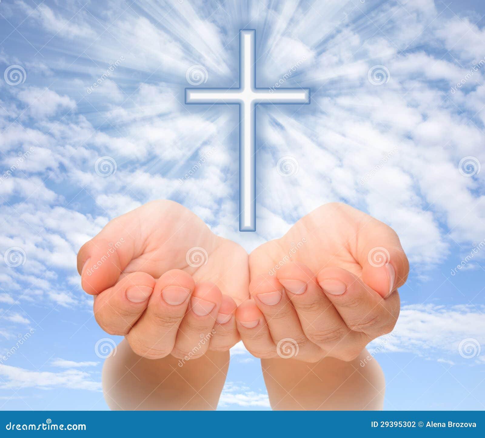 Mains retenant la croix chrétienne avec les faisceaux de lumière