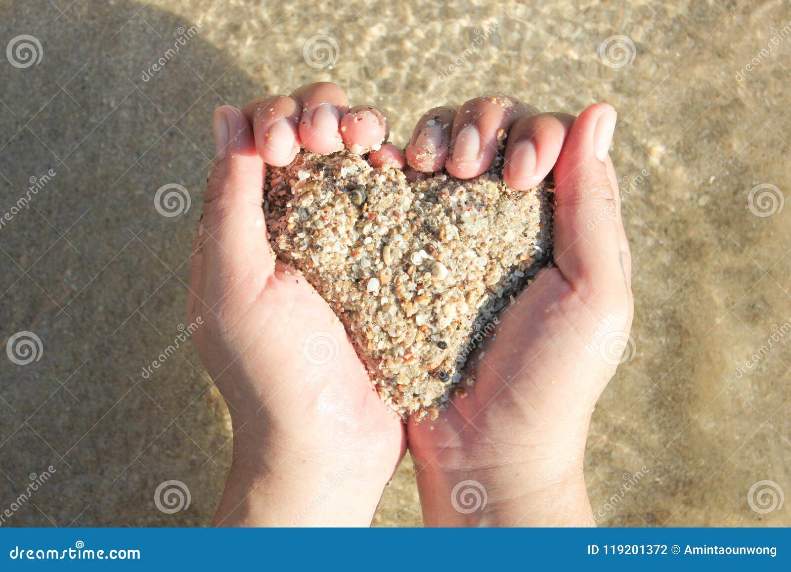 Mains tenant un sable sous la forme du coeur