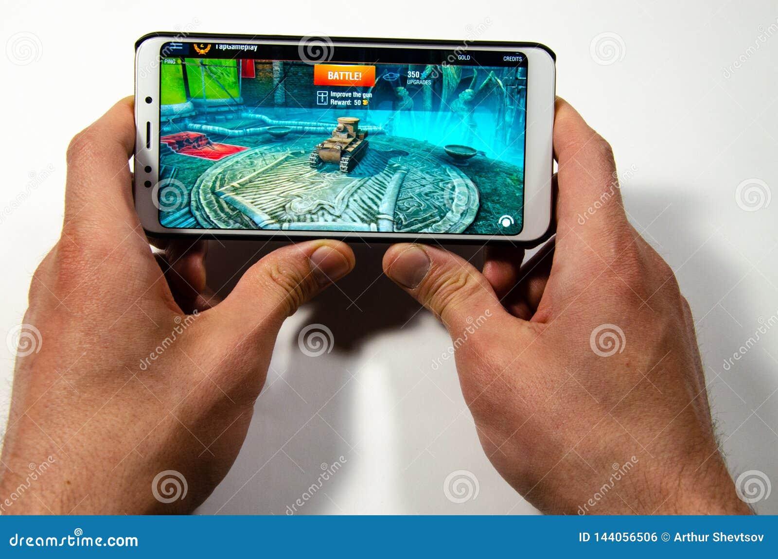 Mains tenant un smartphone sur lequel le jeu, monde gameplay de Gameplay d attaque éclaire de réservoirs