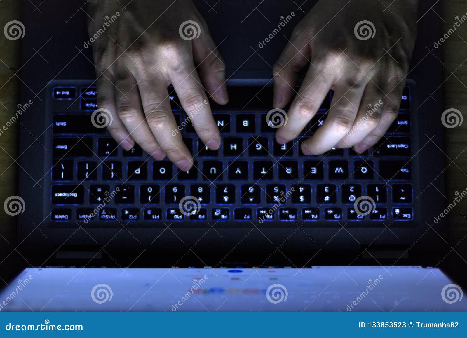 Mains utilisant l ordinateur portable dans l obscurité