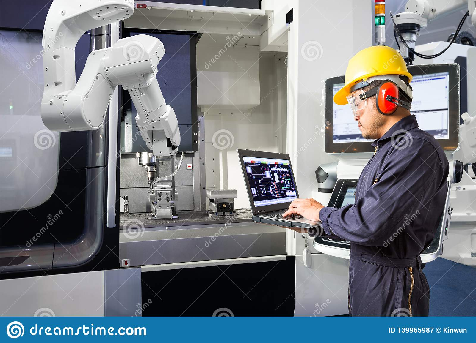 Maintenance engineer using laptop computer control automatic robotic hand with CNC machine in smart factory, Industry 4.0 concept