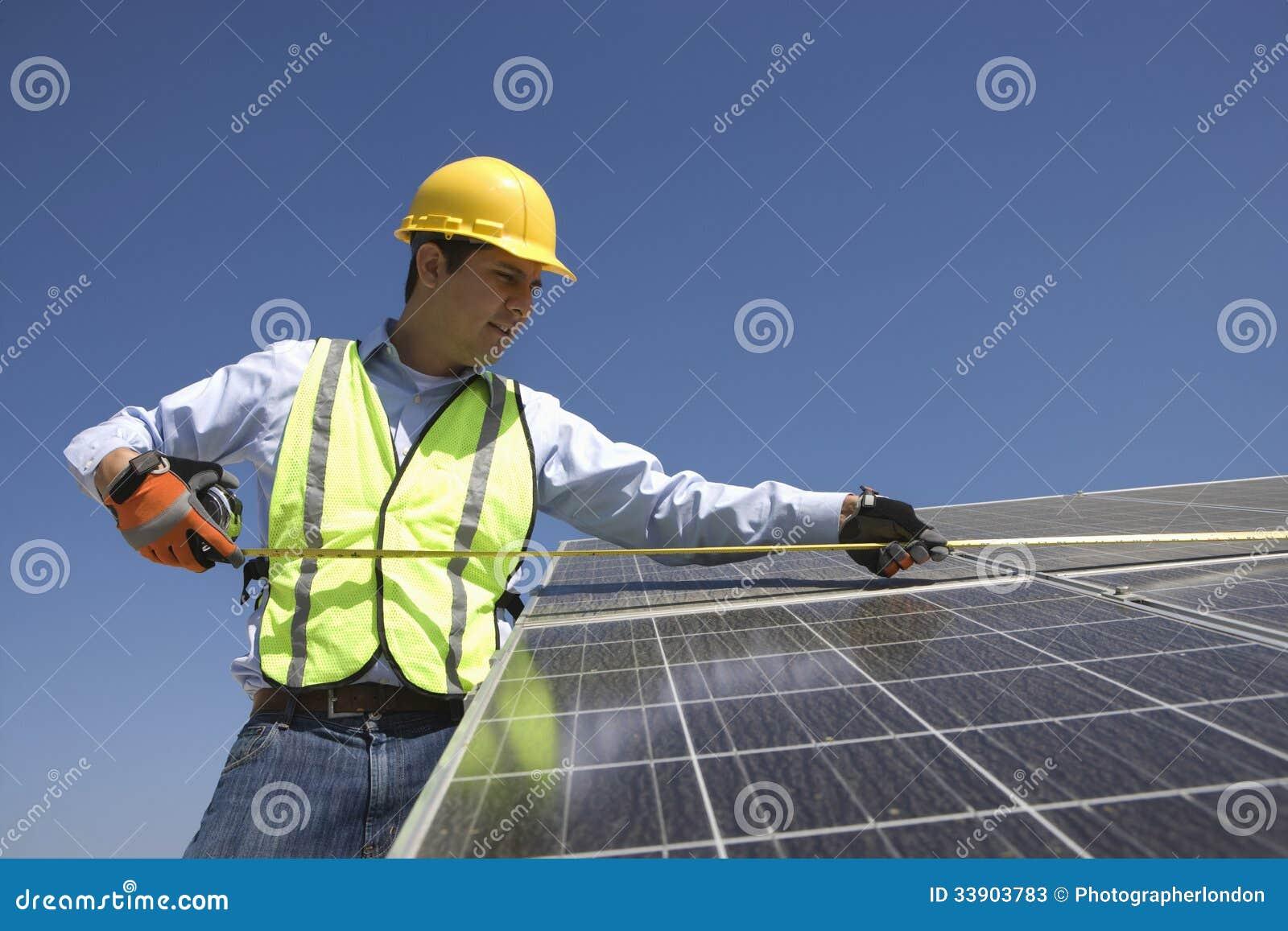 Maintenance Worker Measuring Solar Cells Stock Image