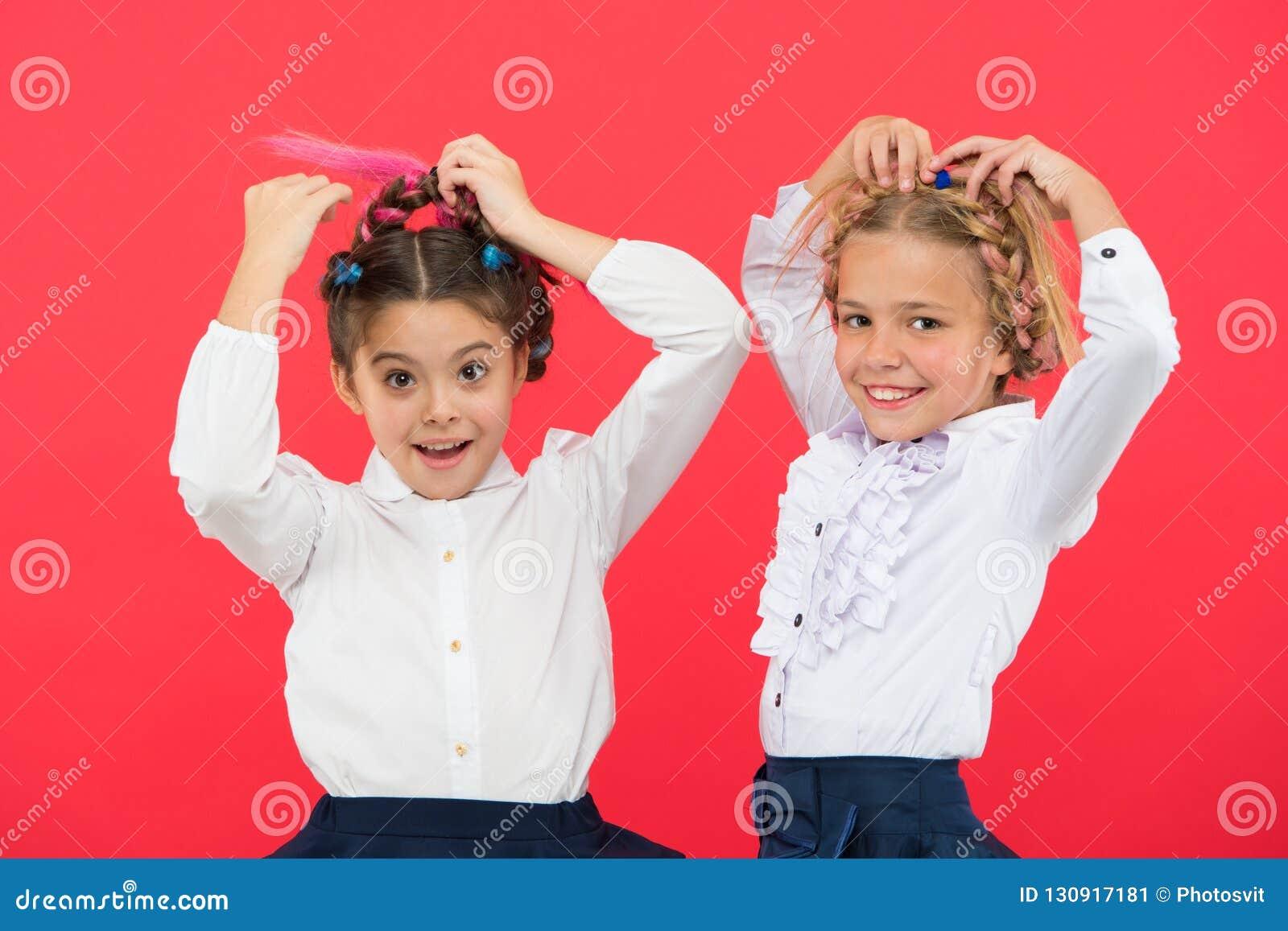Maintenez les cheveux tressés pour le regard rangé Les élèves d enfants jouent avec de longs cheveux tressés Salon de coiffeur Co