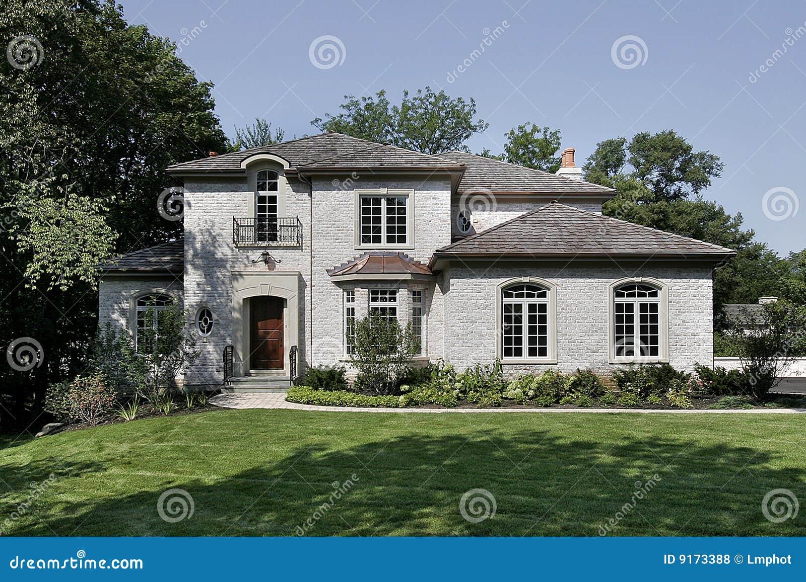 Maison blanche de brique avec le toit de secousse de c dre for Maison en brique blanche