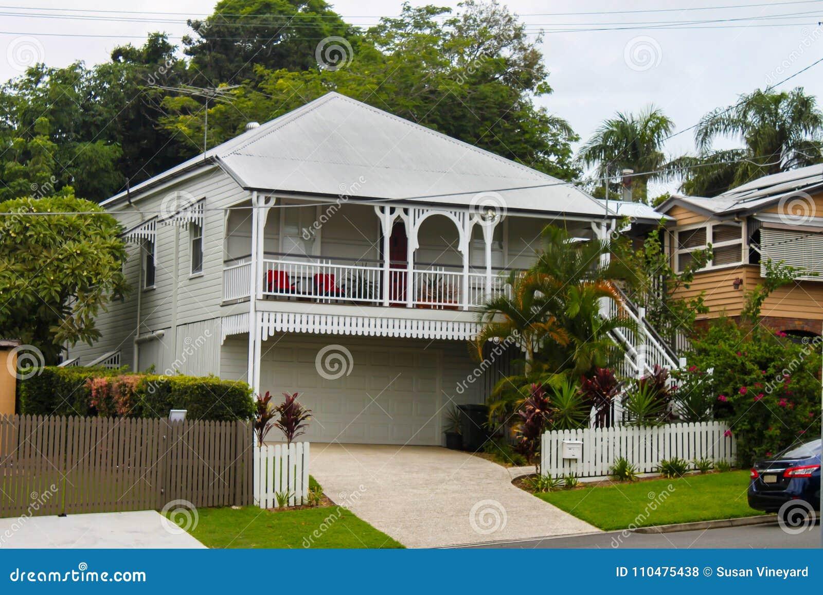 Maison blanche de queenslander avec la verdure tropicale et arbres grands le jour obscurci dans l