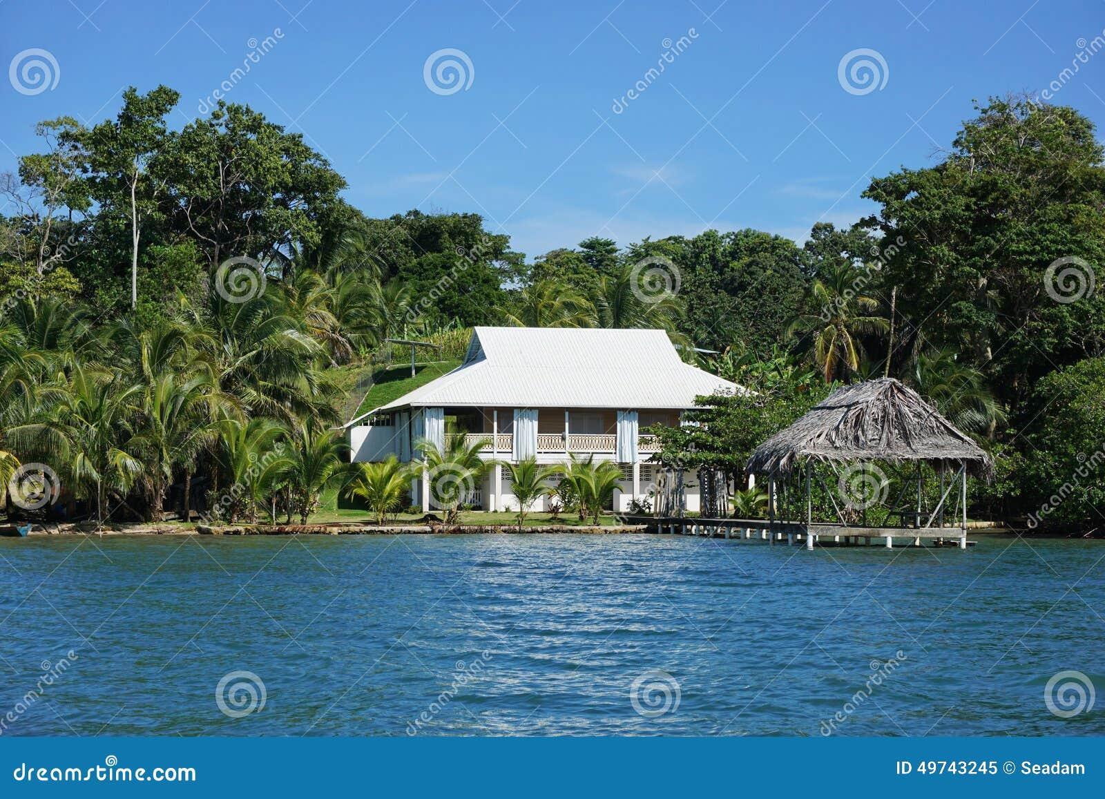 maison de bord de mer avec la hutte couverte de chaume au. Black Bedroom Furniture Sets. Home Design Ideas