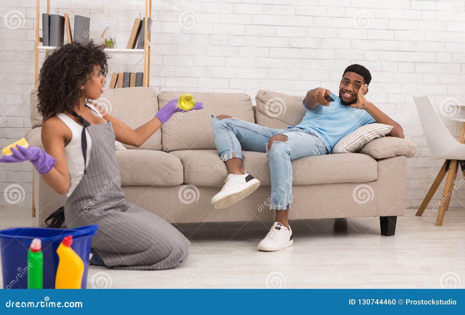 Maison de nettoyage de femme tandis que son ami se reposant sur le divan