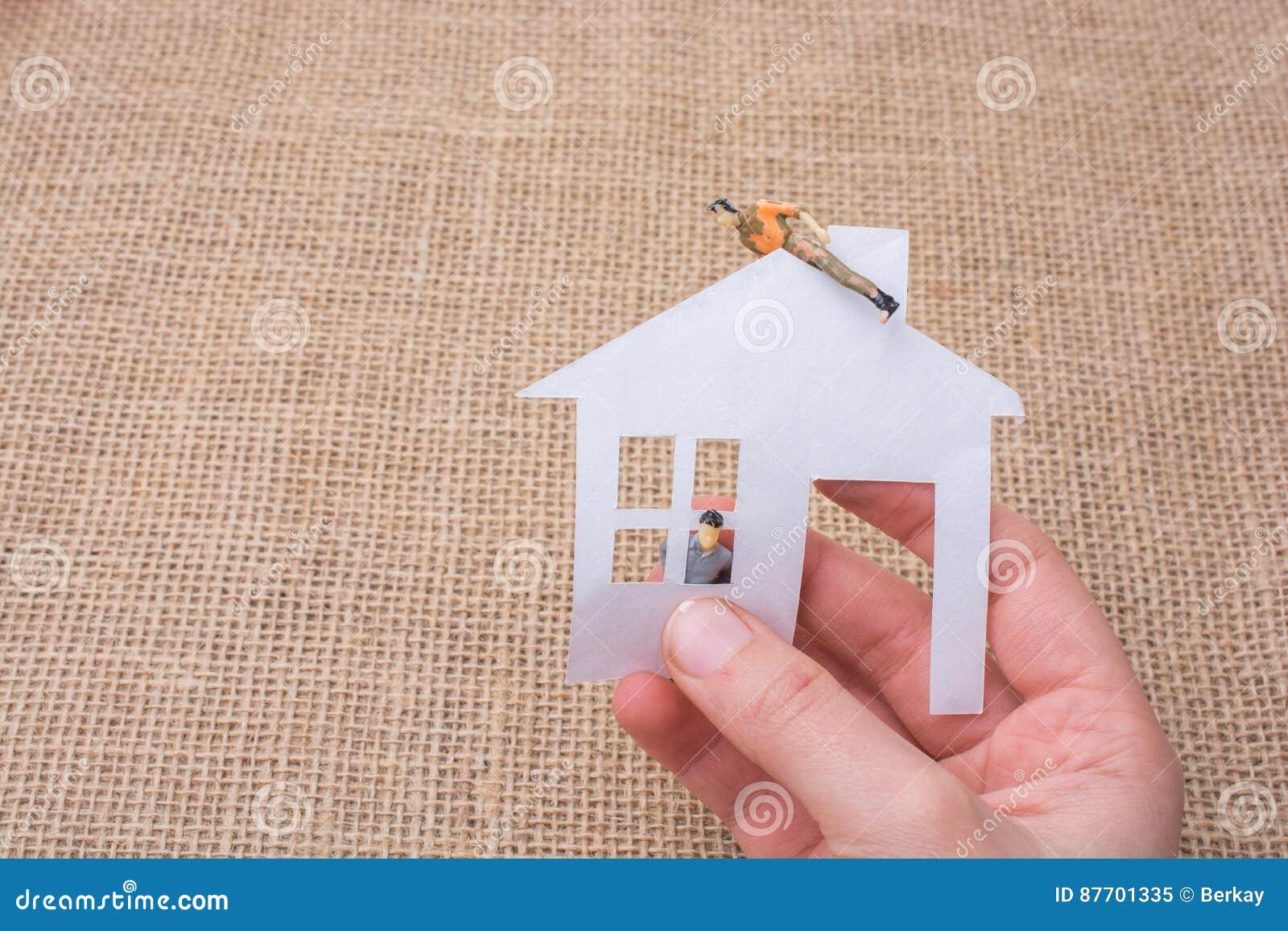 Maison de papier et une figurine d homme sur un fond de toile