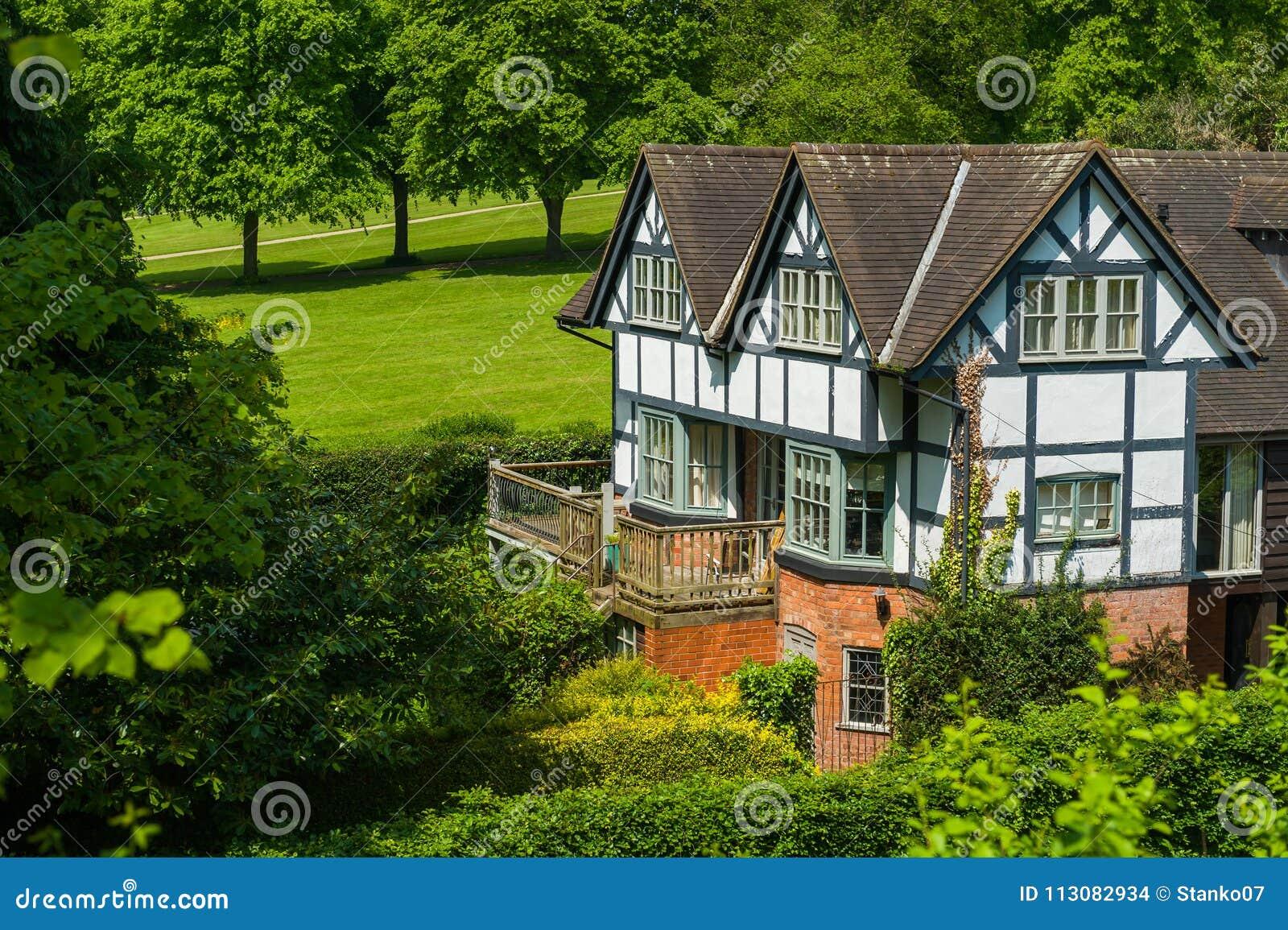 Maison de Tudor entourée par des arbres et des arbustes