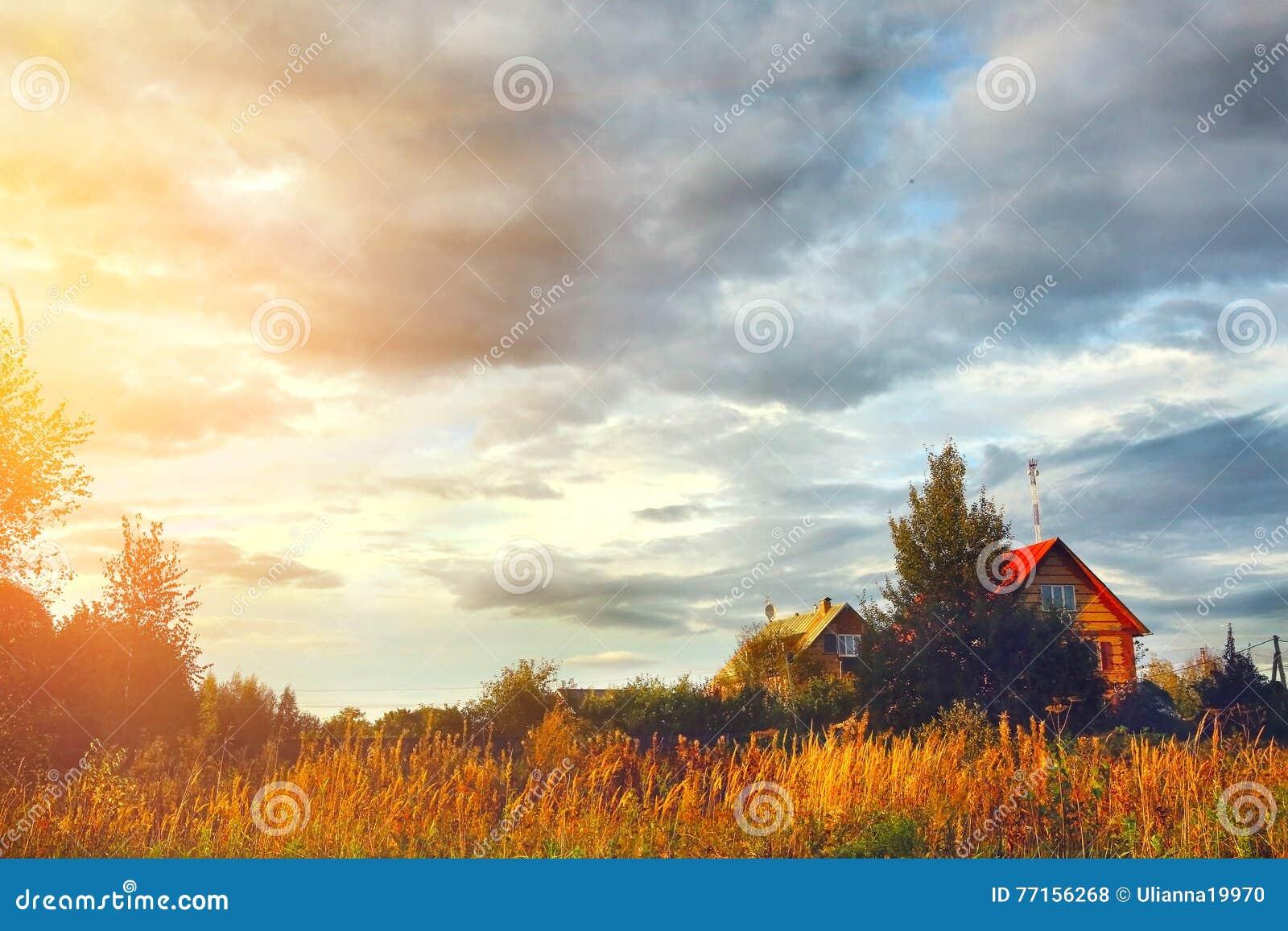 Maison de village sur le champ et le ciel nuageux