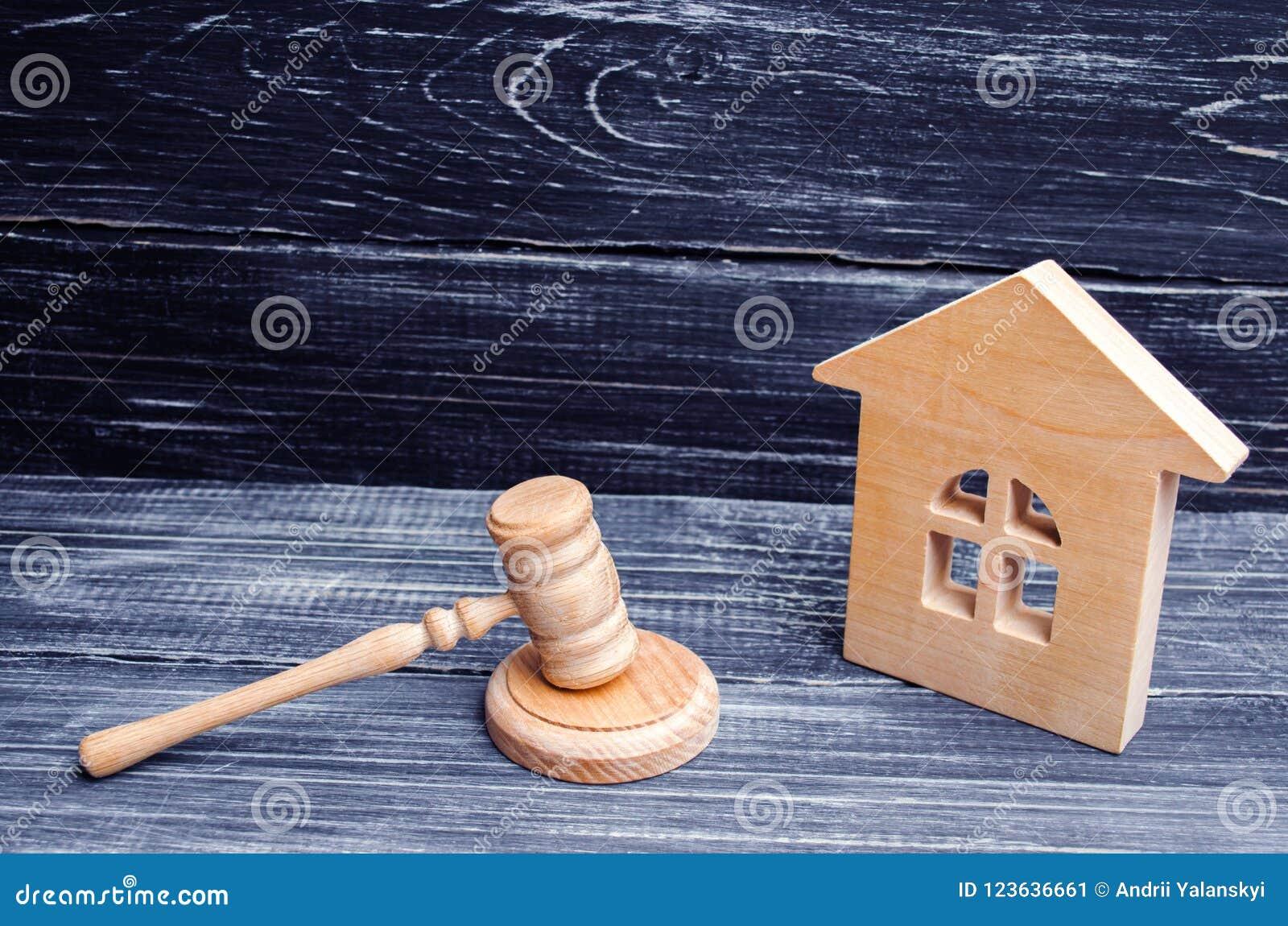 Maison en bois et un marteau du juge sur un fond noir Affaires en jugement sur la propriété et les immobiliers Confiscation et na