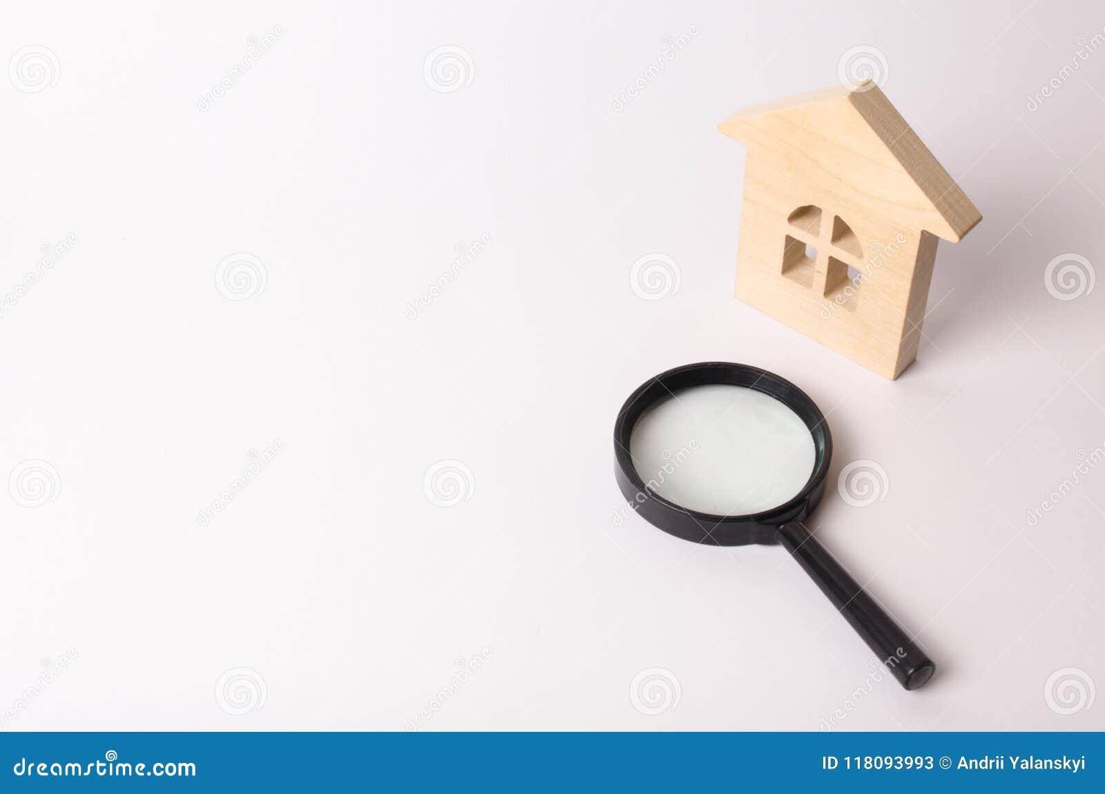 Maison en bois et une loupe sur un fond blanc Le concept de trouver une maison, d acheter ou de louer un appartement realtor