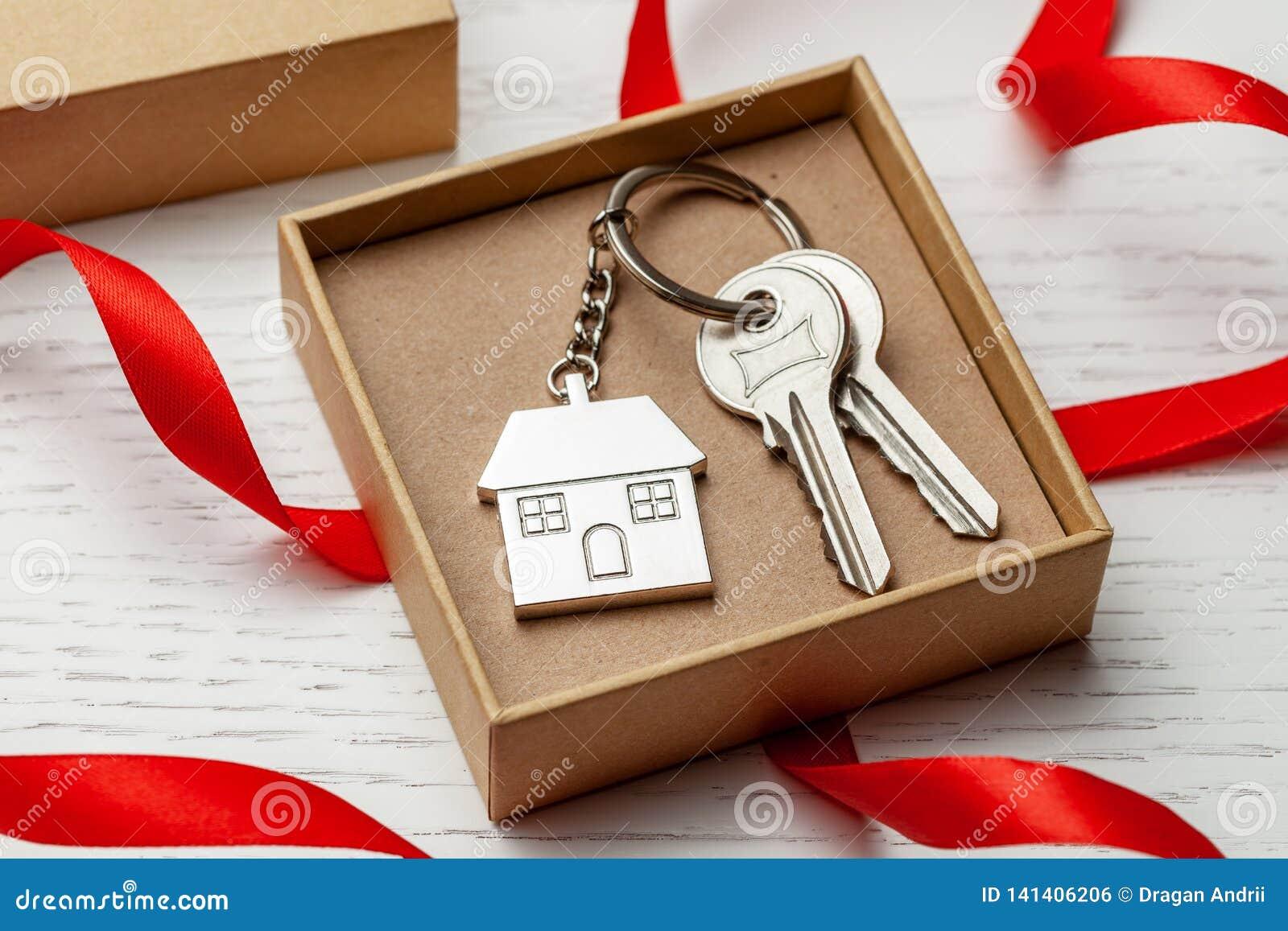 Maison et clés de Keychain avec le ruban et le boîte-cadeau rouges sur le fond en bois blanc
