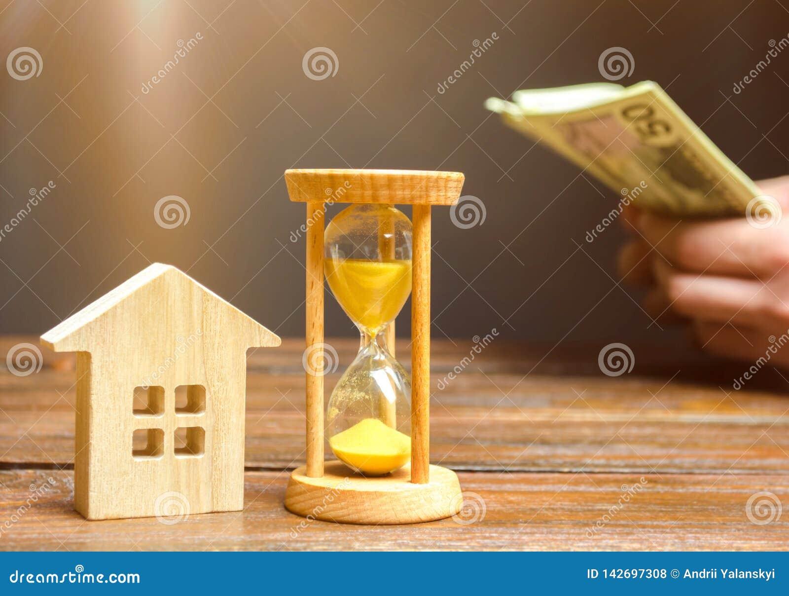 Maison et horloge en bois Homme d affaires comptant l argent Paiement de d?p?t ou paiement par anticipation pour louer une maison