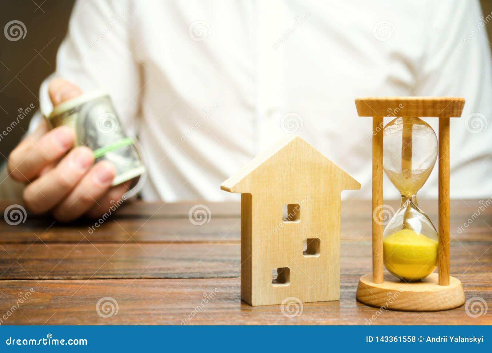 Maison et horloge en bois L homme d affaires retient l argent Paiement de dépôt ou paiement par anticipation pour louer une maiso