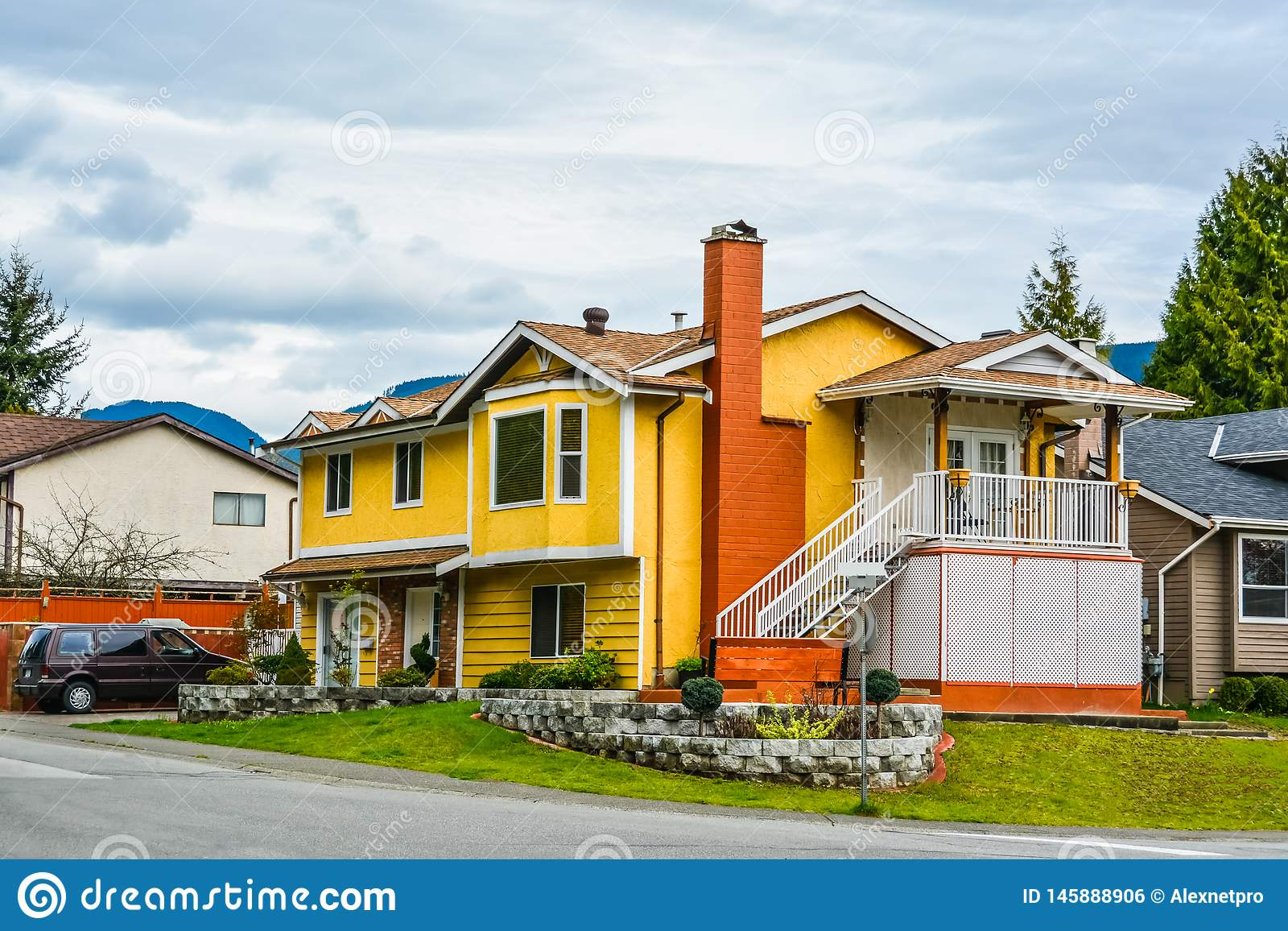Maison jaune de famille avec une voiture sur l allée sur le fond de ciel nuageux