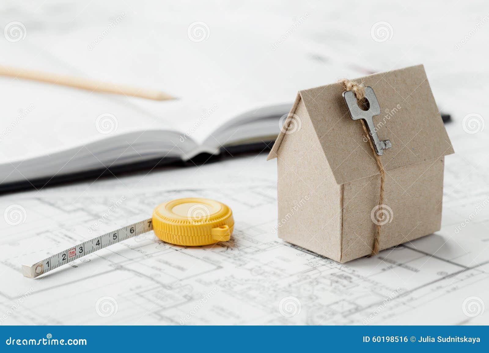 Maison modèle de carton avec la clé et le ruban métrique sur le modèle Concept de construction individuelle, architectural et de