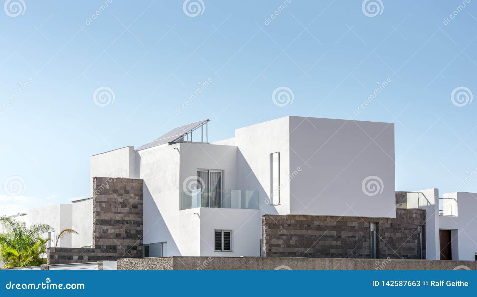 Maison résidentielle luxueuse avec l architecture moderne devant le ciel ensoleillé