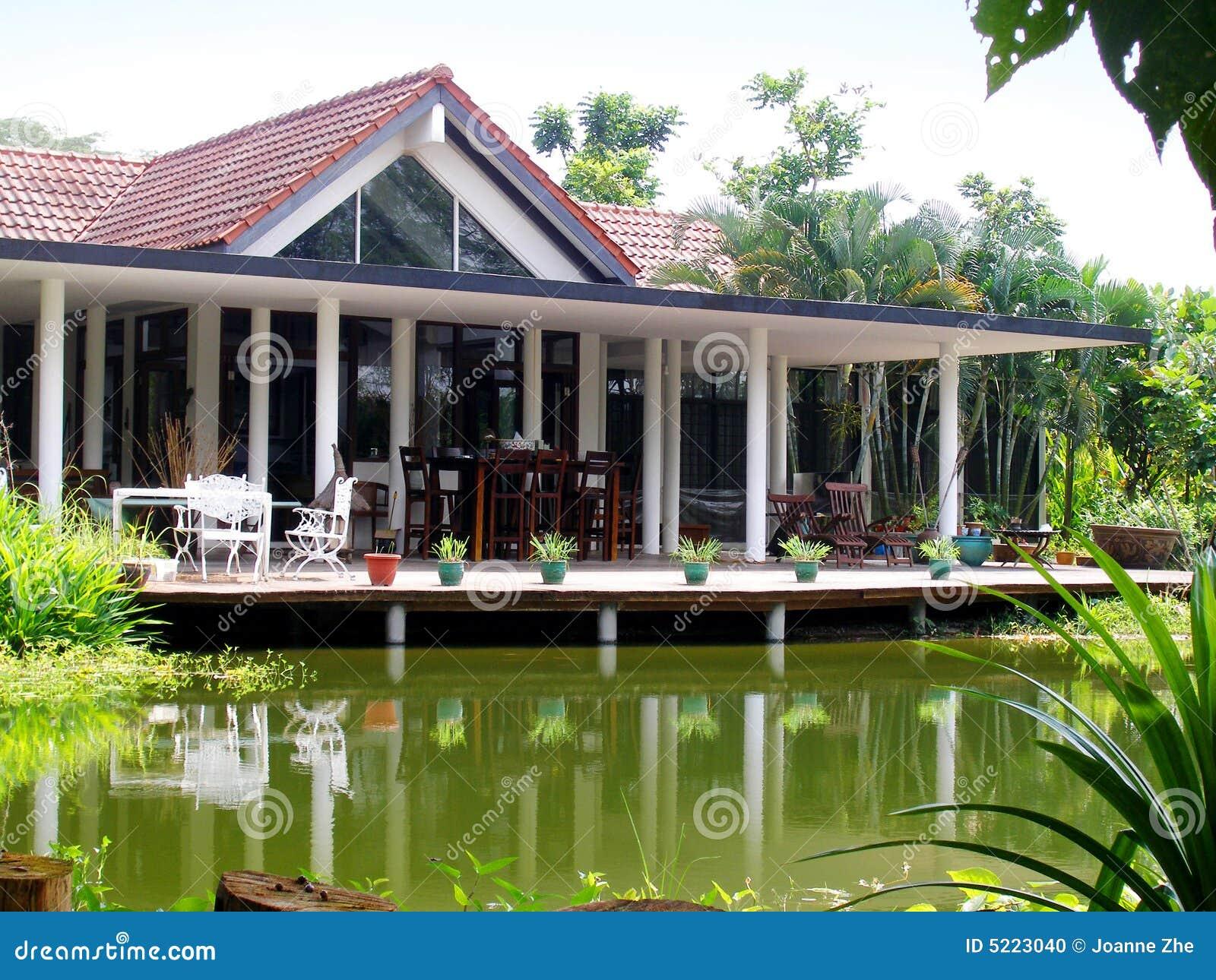 Maison tropicale et étang normal