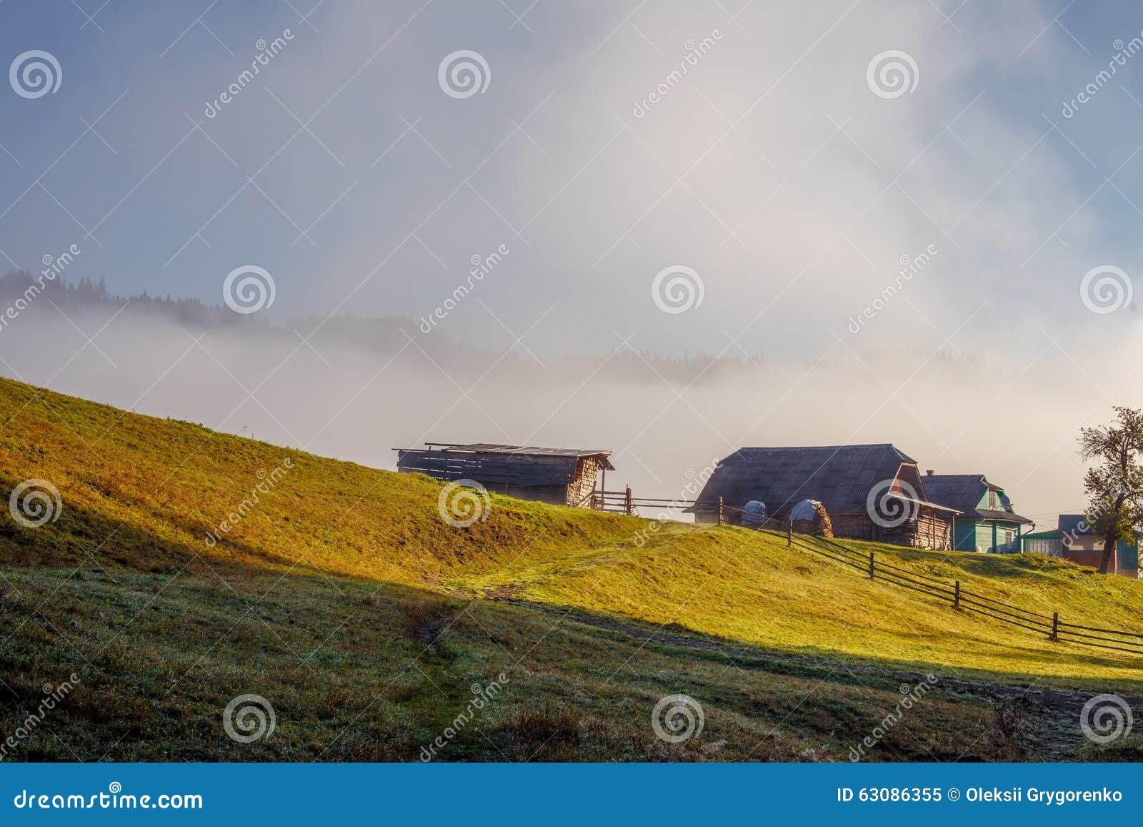 Download Maisons En Bois Sur La Colline Sur Le Fond De Brouillard Image stock - Image du gouttelette, couleur: 63086355