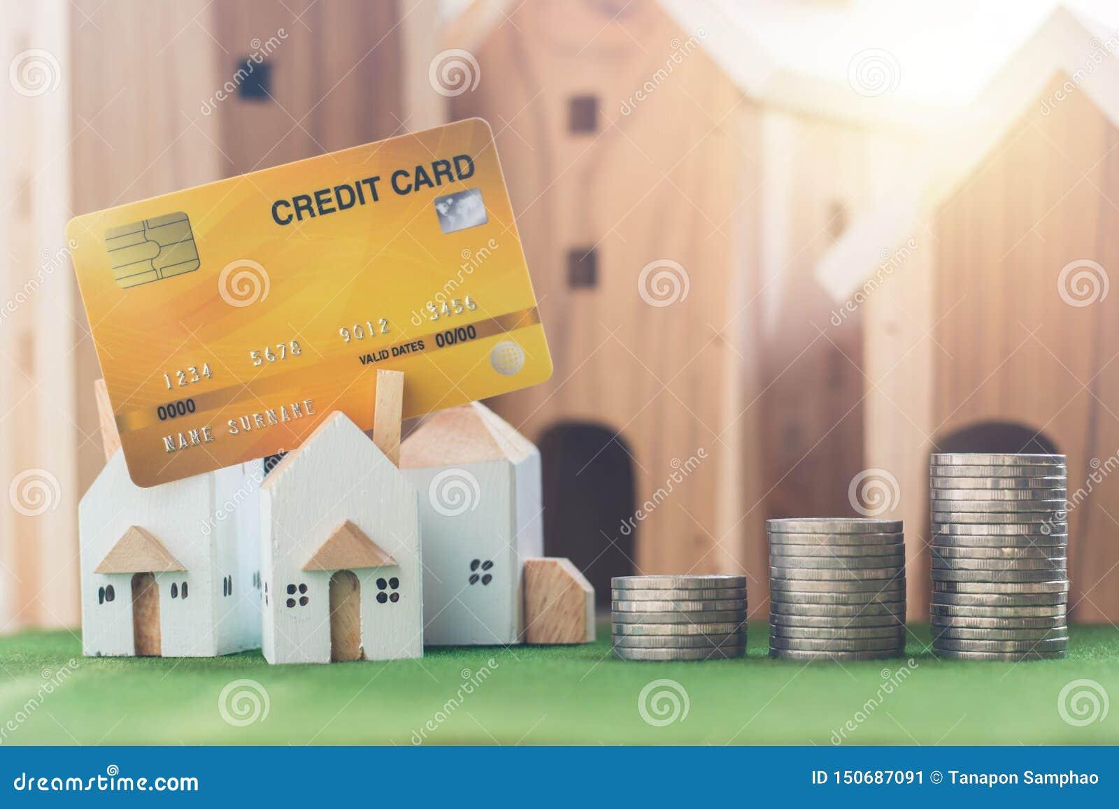 Majątkowa inwestycja, miniatura dom model z kartą kredytową, i pieniądze monety sterta na symulacji trawie