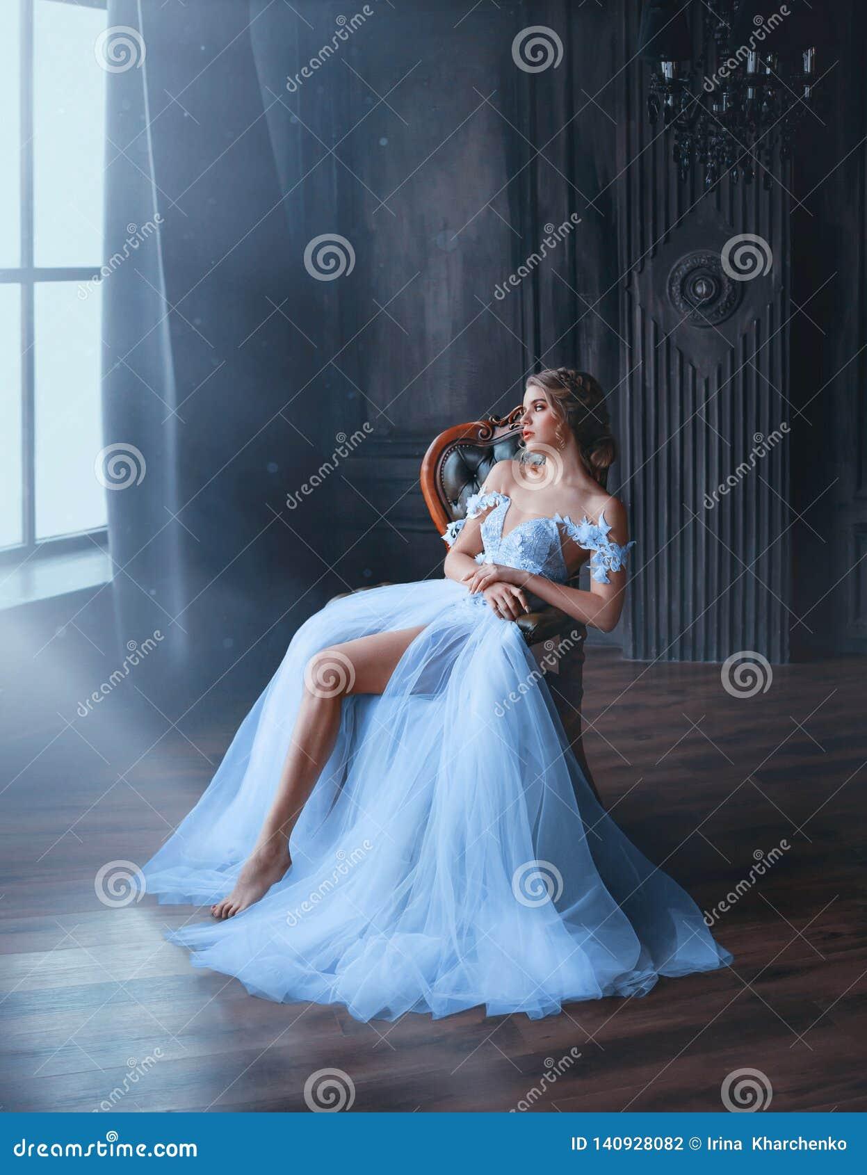 Majestatyczna i dumna princess dziewczyna w biała modna orientalna suknia męczącym błękita obsiadaniu na krześle, dama pokazuje d