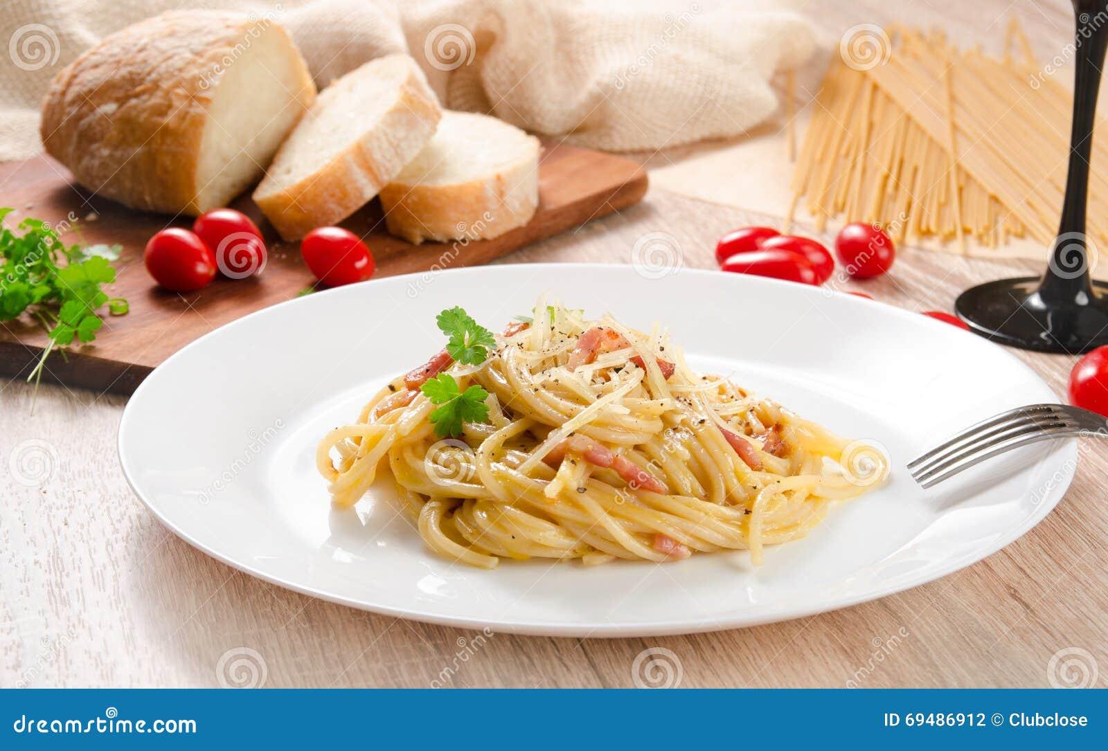 Makaron Carbonara z bekonem na białym talerzu, drewniany stół