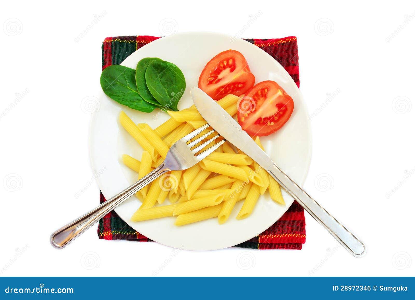Makaron, pomidory i szpinak na talerzu,