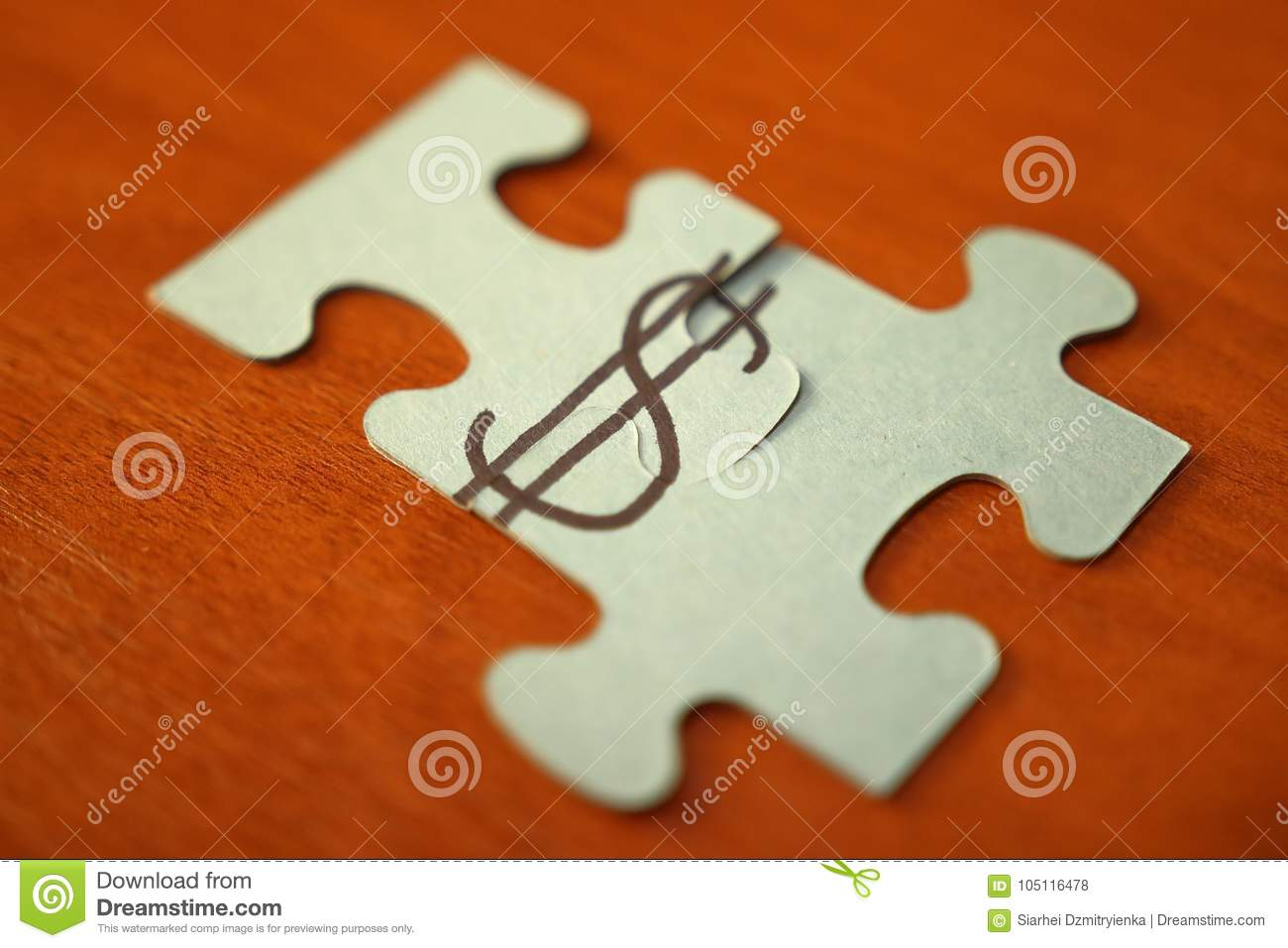 Make money concept. Puzzles puts in dollar sign. dollar sign on two parts of puzzle on wooden table. Money, capital, business.