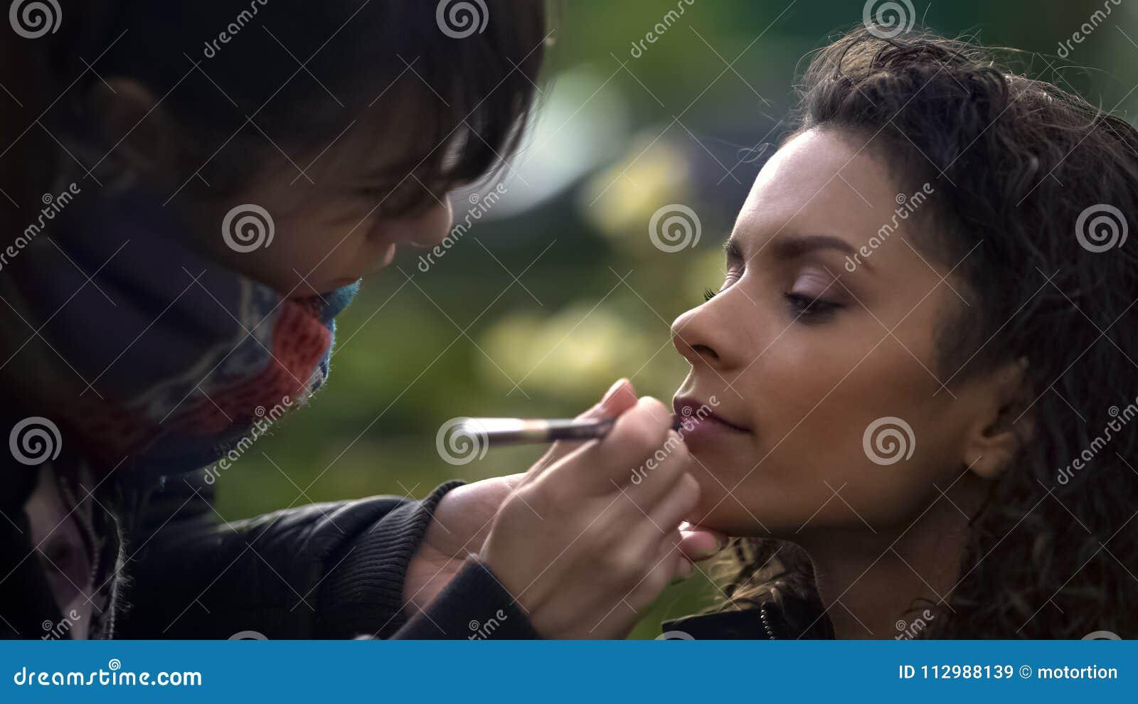 Make-up artist applying lipstick on models lips, natural beauty of biracial lady