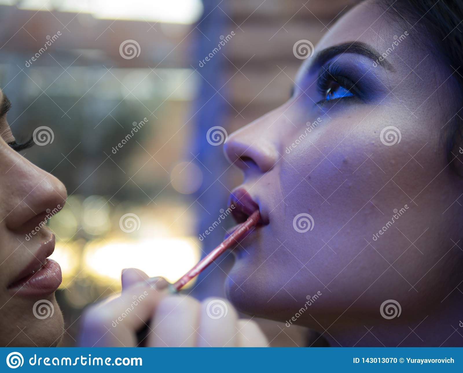 The make up artist does make up to the beautiful young woman indoors.lips close up