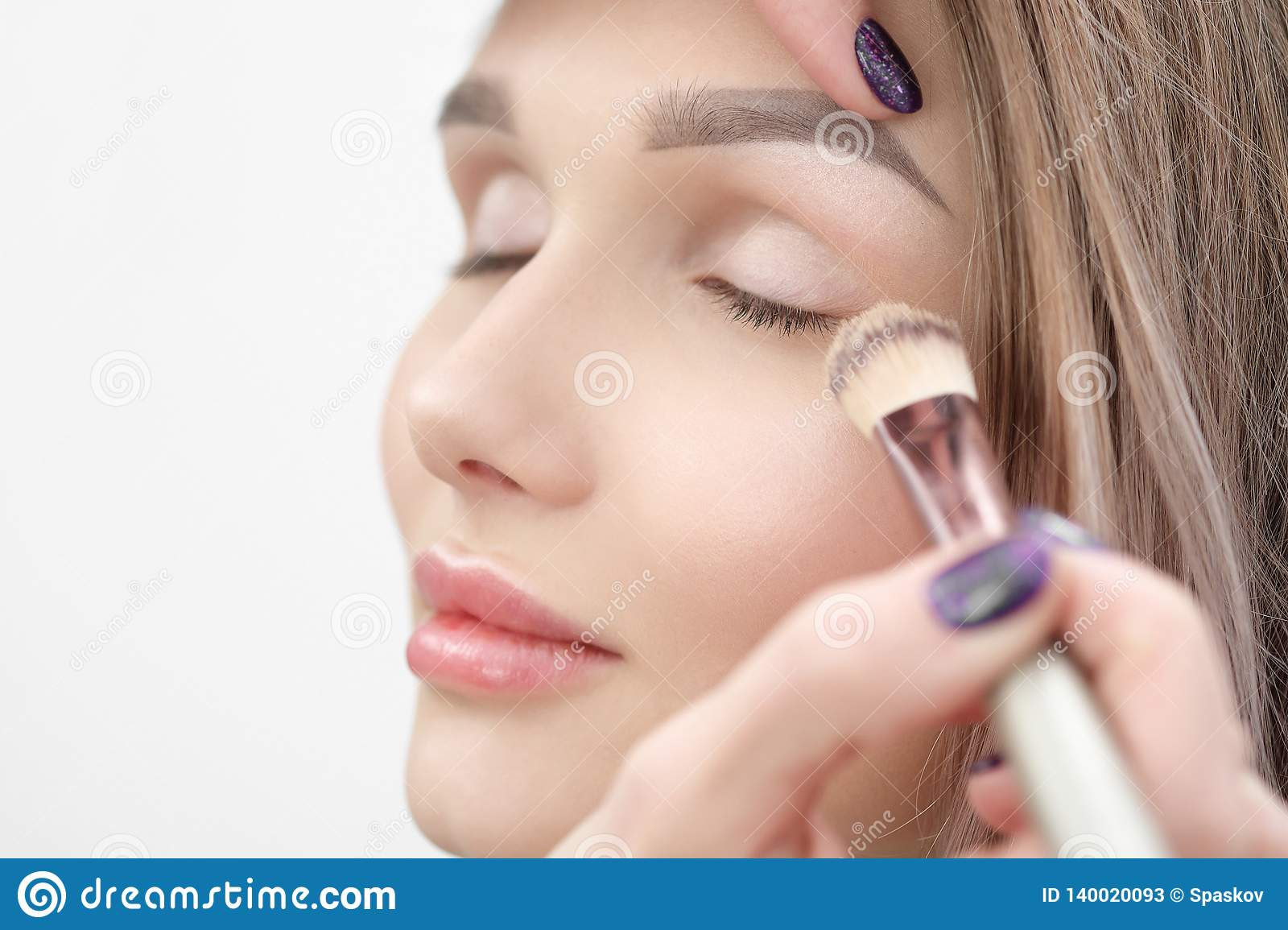 7f2f18734a4 Make-up artist makes makeup beautiful blonde girl on a white background.  Close-