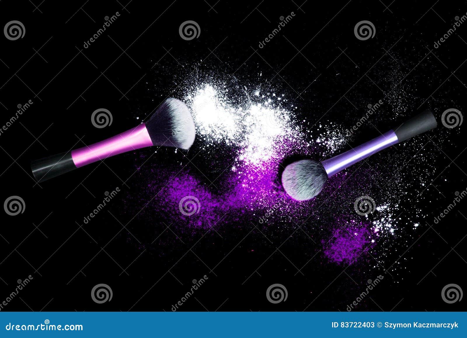 Make-up brush with white powder spilled glitter dust on black background. Makeup brush