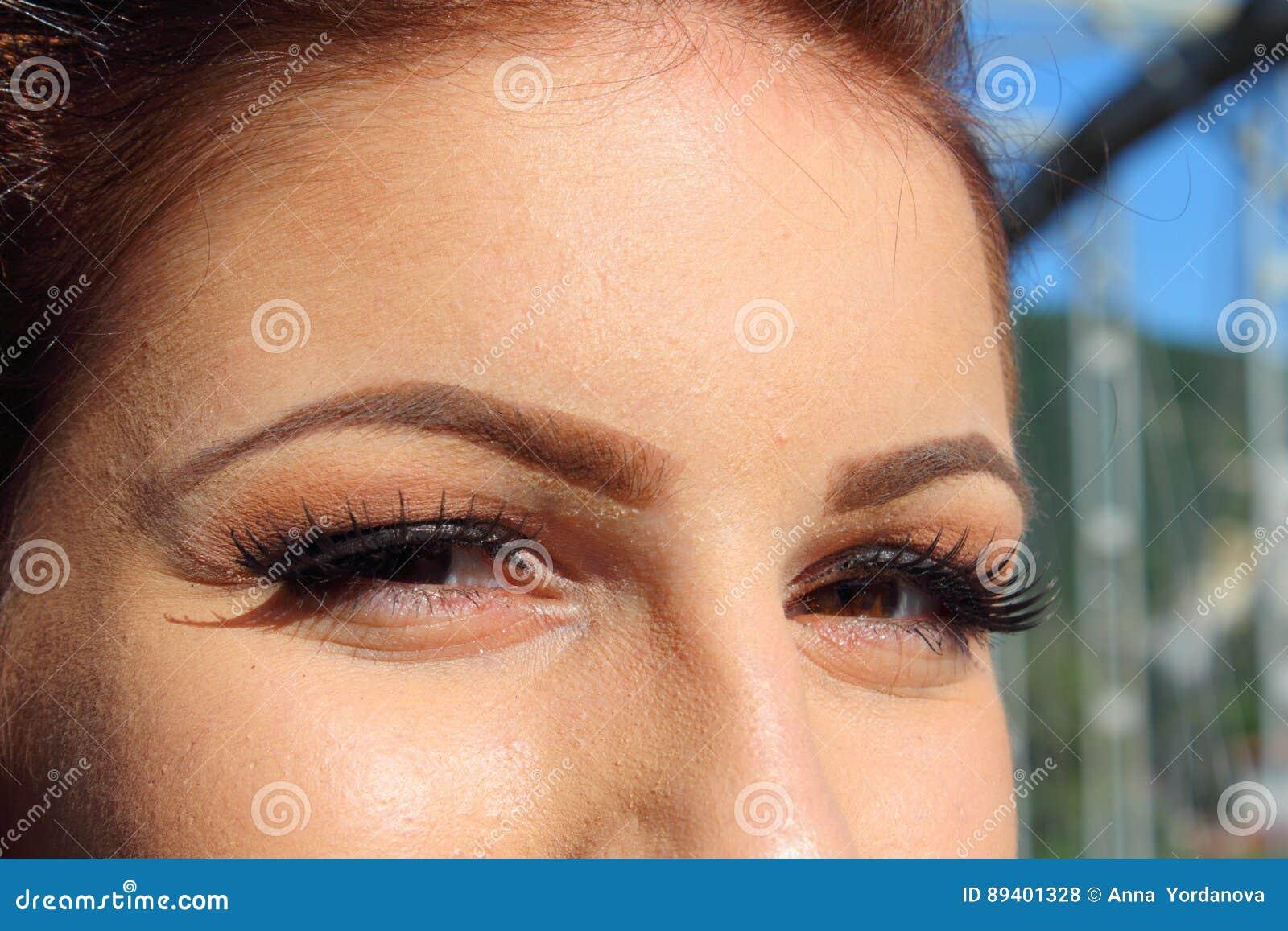 Make-up de jonge vrouw het glimlachen mening van de ogenclose-up