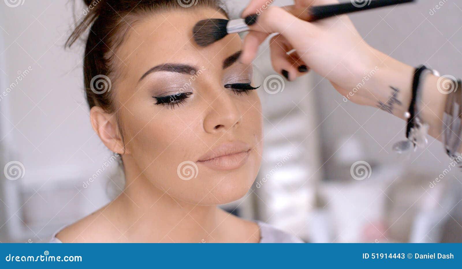 Make-upkunstenaar Applying Lipstick aan Mooie Vrouw