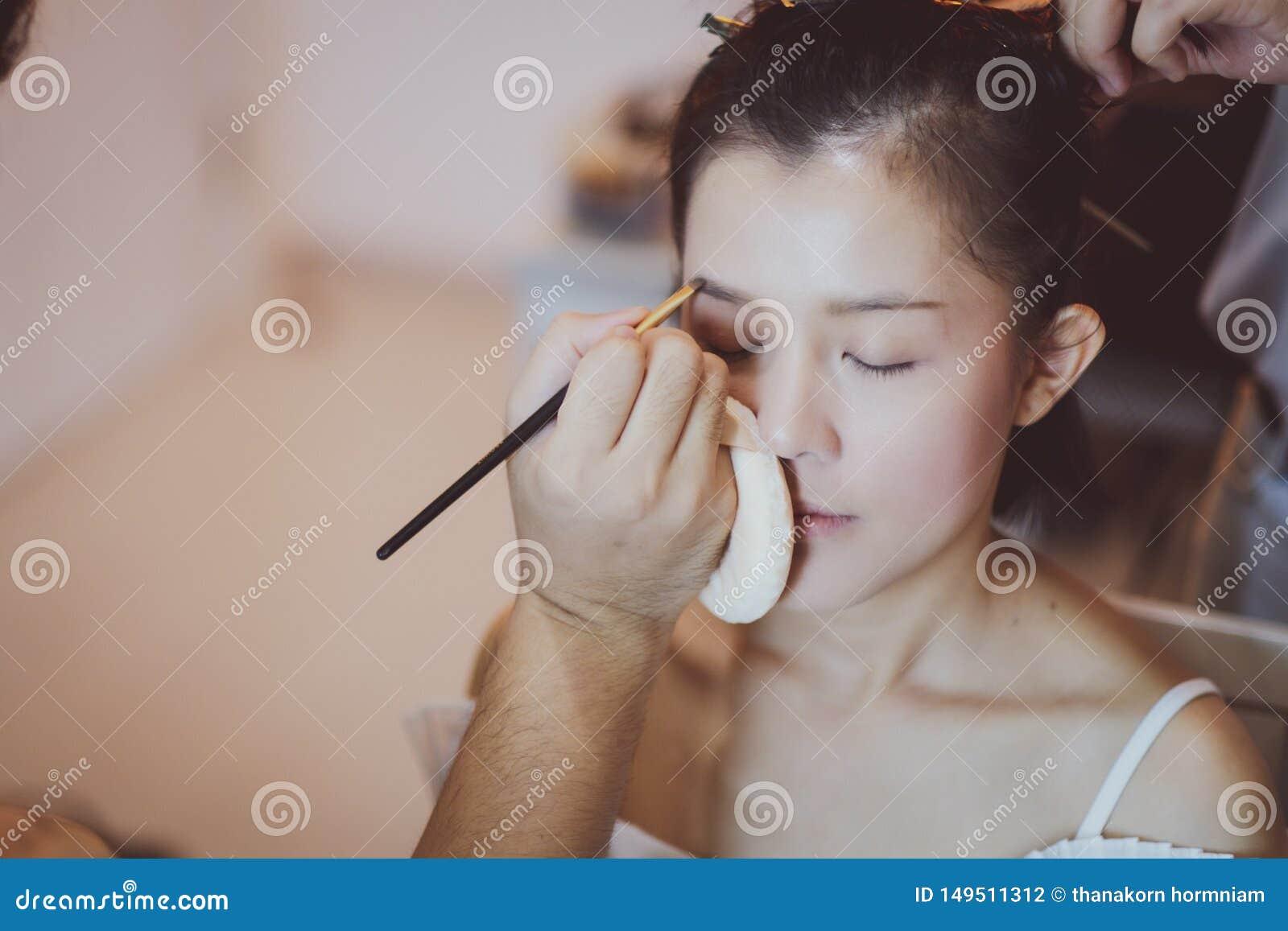 Make-upkunstenaar die aan mooi Aziatisch model werken
