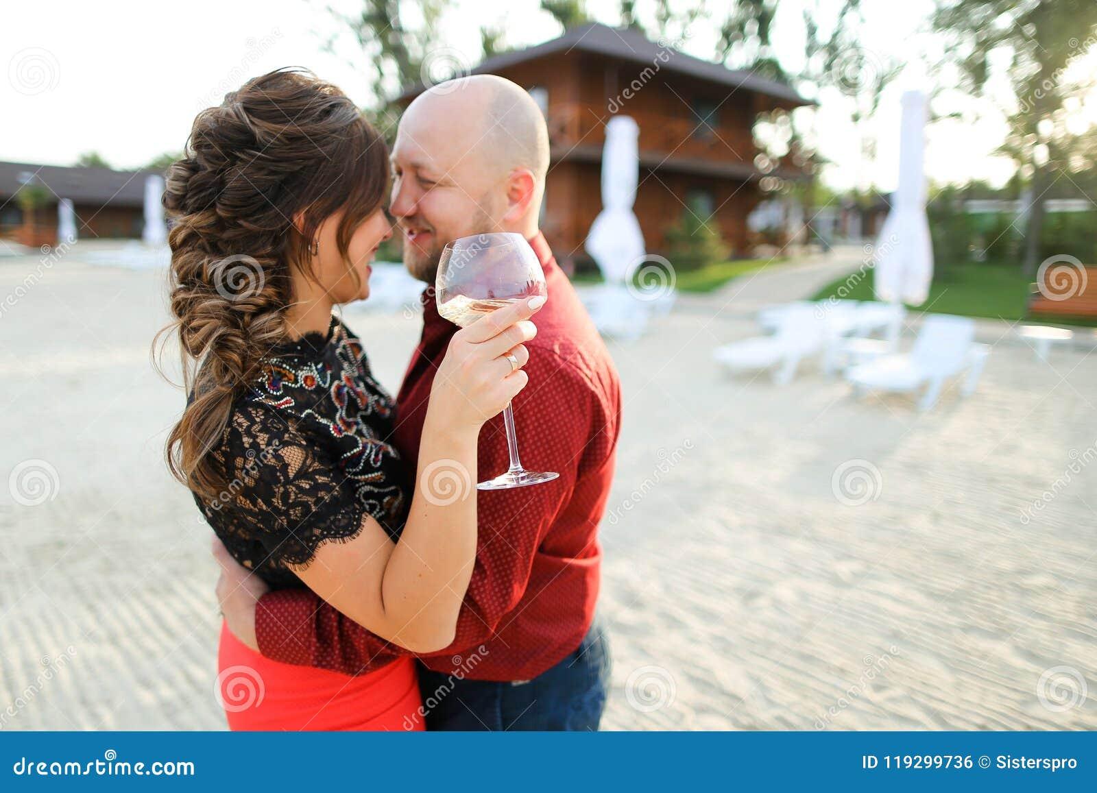 Makedans med frun som håller exponeringsglas av vin på trädgård