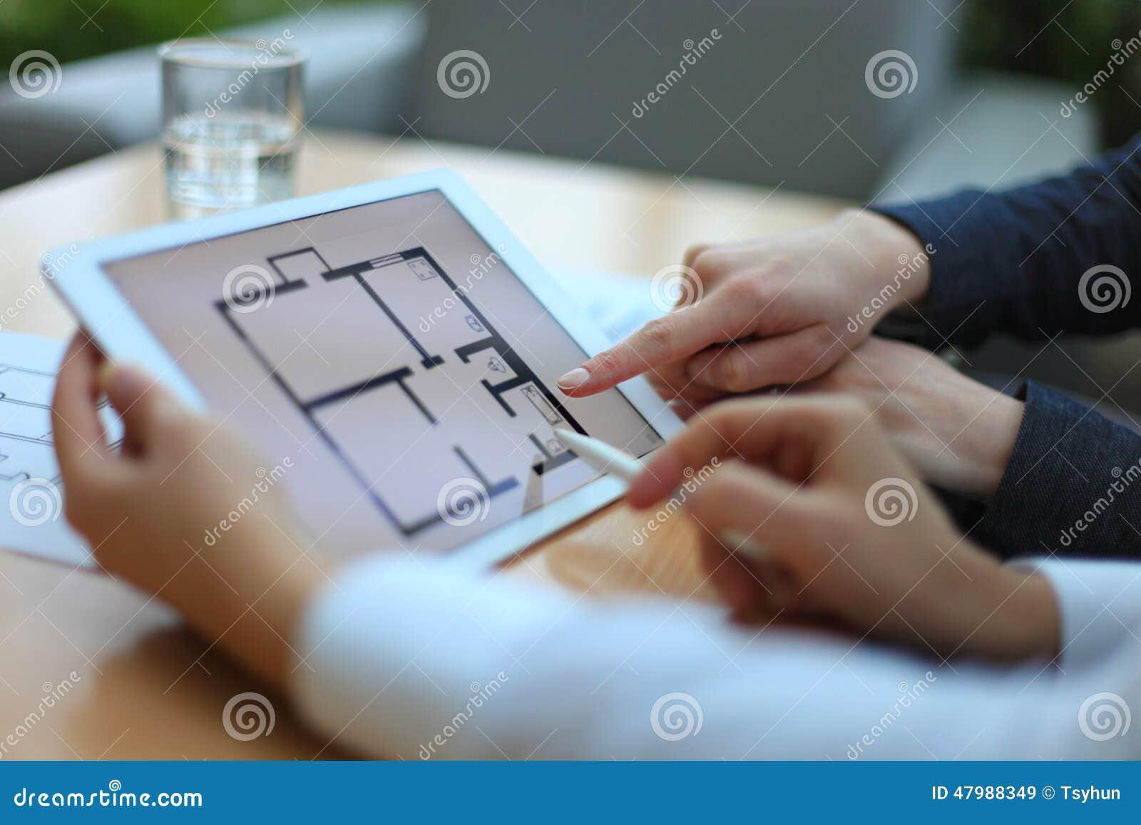 Makelaar in onroerend goed die huisplannen tonen