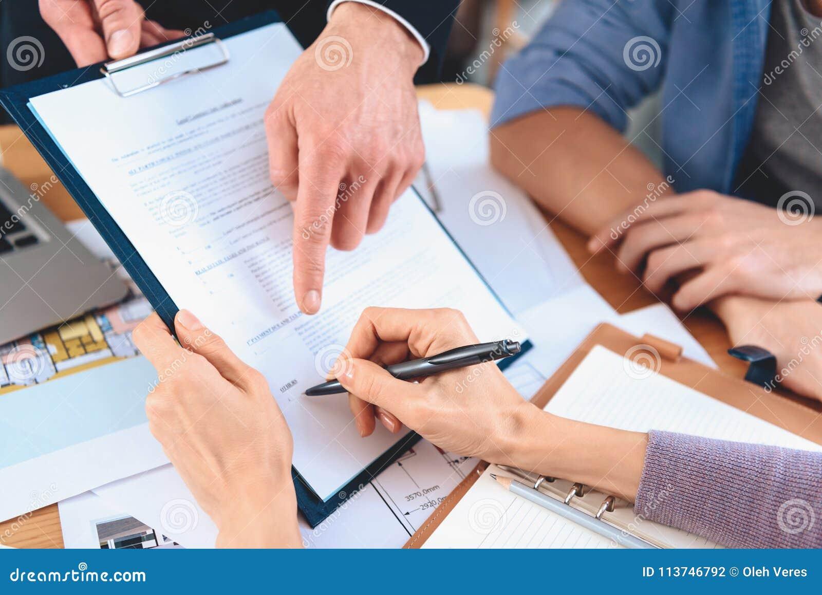 Makelaar in onroerend goedzitting bij bureau in bureau De moeder ondertekent contract voor nieuwe flat
