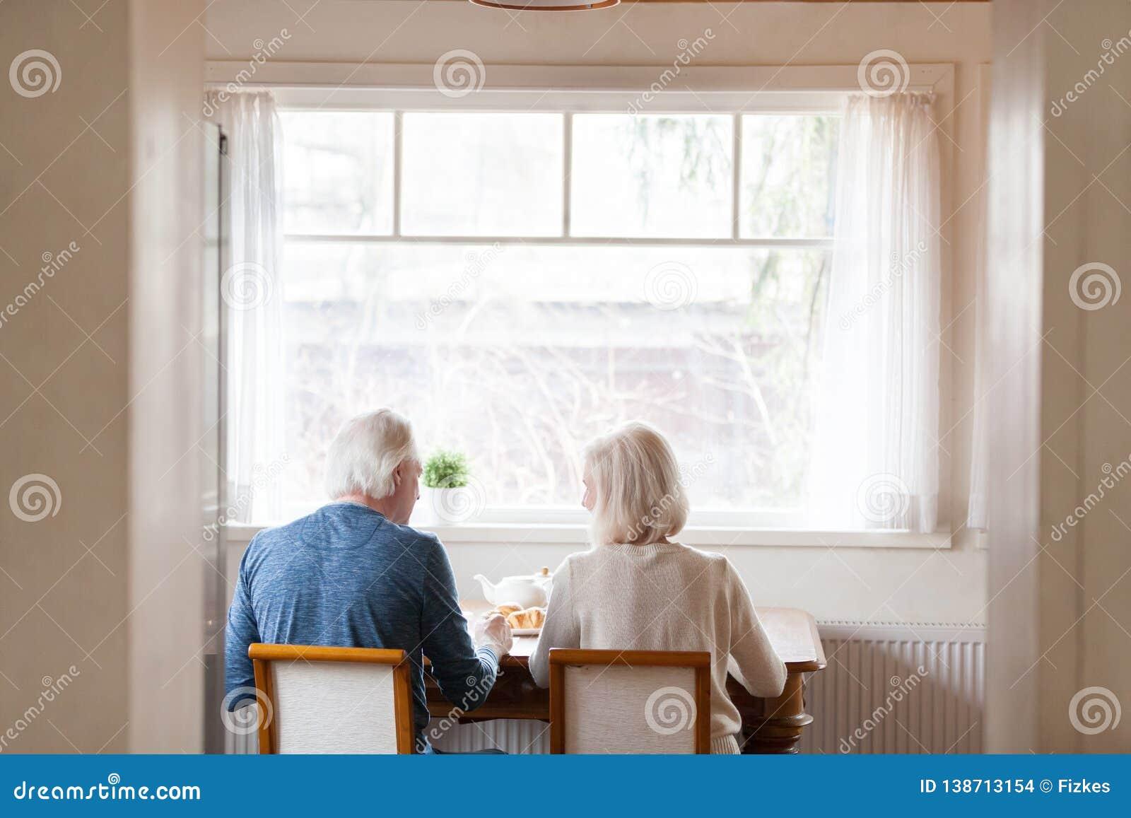 Maker för bakre sikt som sitter på stolar på den äta middag tabellen