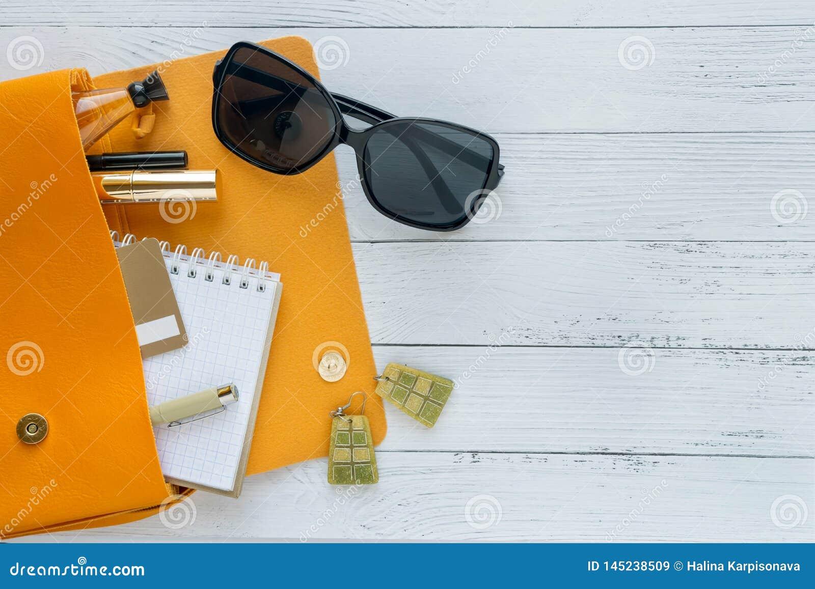 Έννοια μόδας Θηλυκά πράγματα, καλλυντικά προϊόντα, sunglass, σημειωματάριο και πορτοκαλιά τσάντα στο ξύλινο υπόβαθρο με το copysp