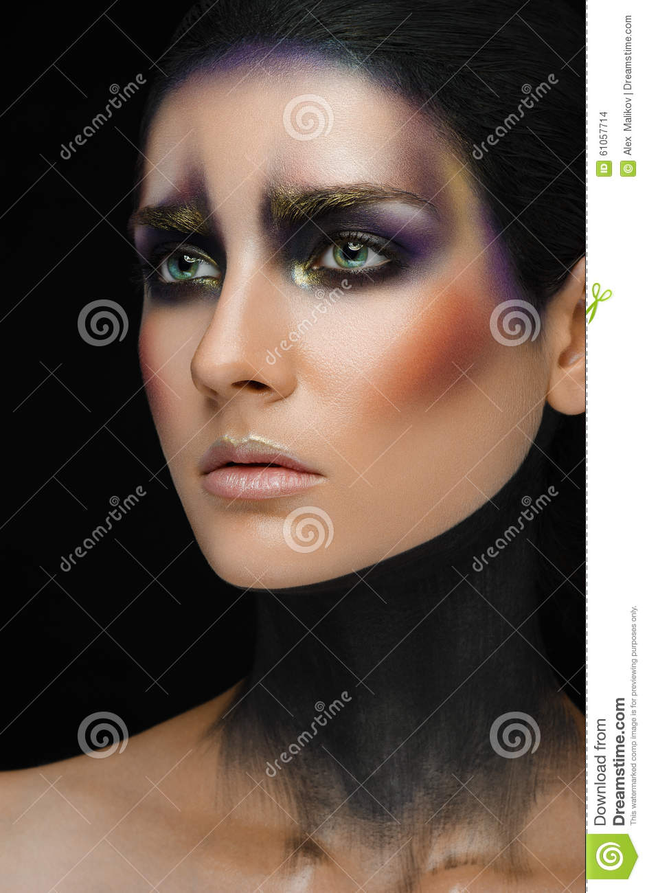 Makeup art and beautiful model theme: beautiful girl with a creative make-up black-and-purple and gold colors on a black backgroun