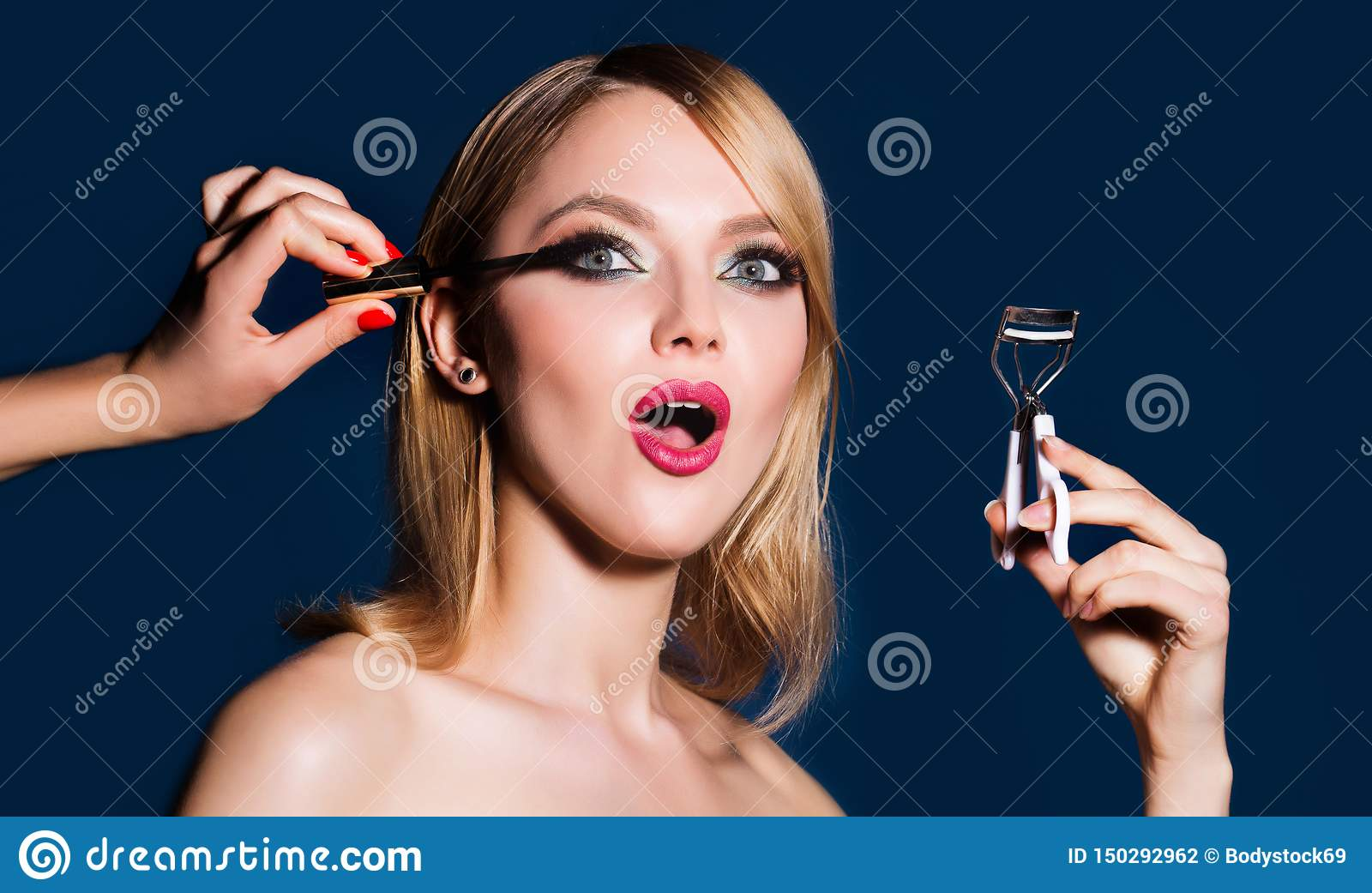 Makeup artist applies mascara to the eyelashes. Bright red lips makeup, perfect clean skin, eye shadows. Woman doing her