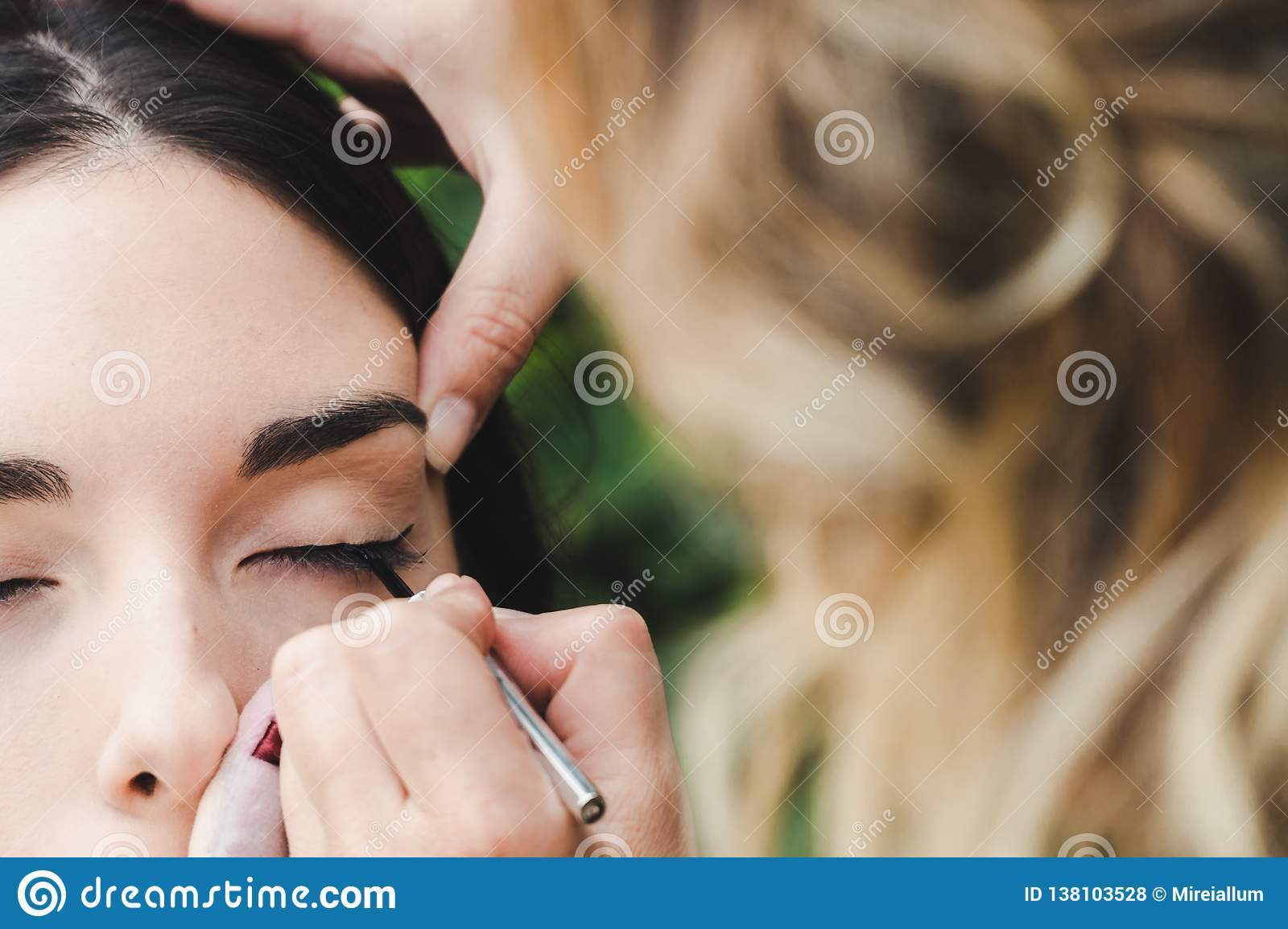 A makeup artist is drawing the eye line to a model. It is a close up image
