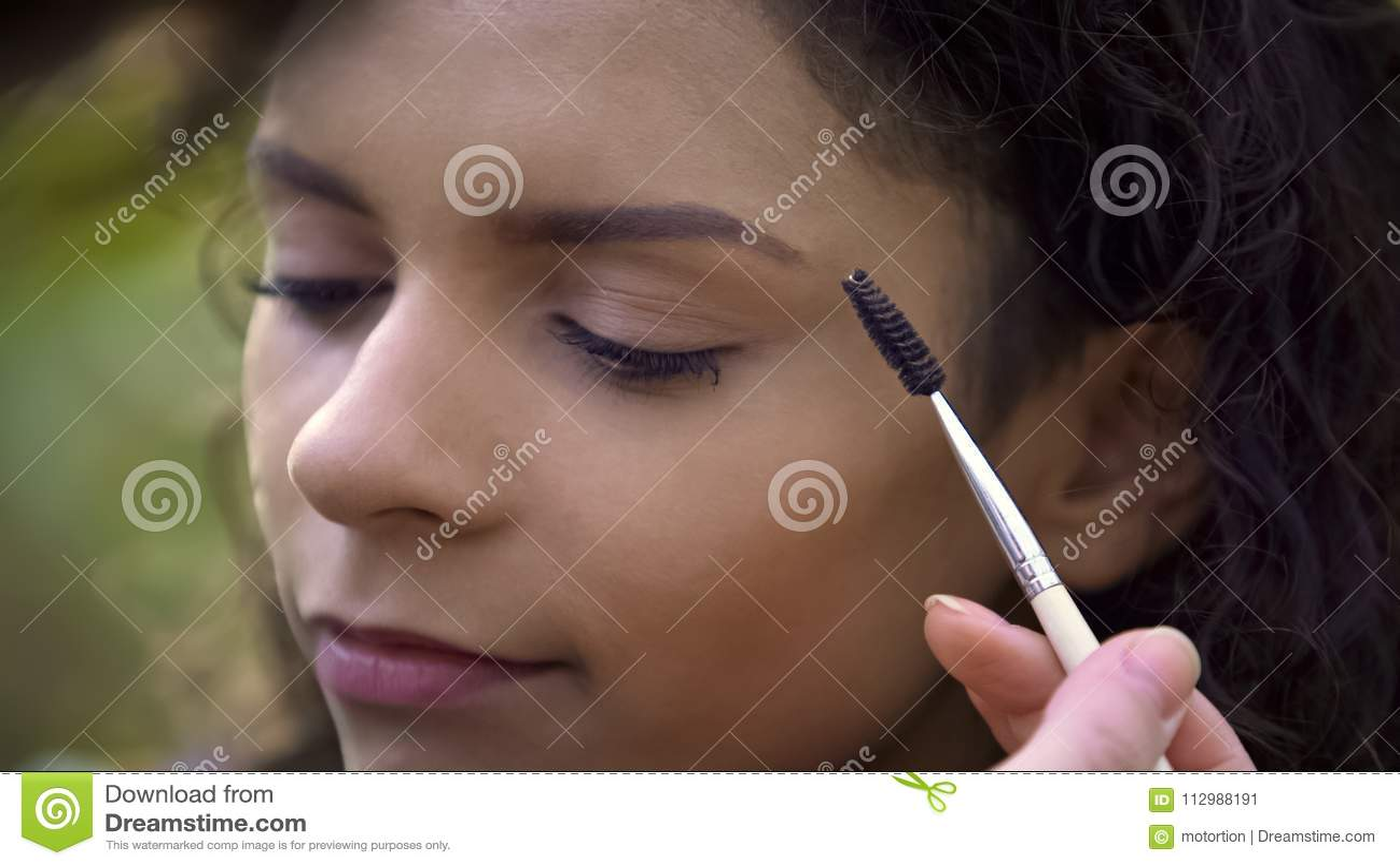 Makeup artist preparing beautiful young woman for shoot, enhancing eyebrows
