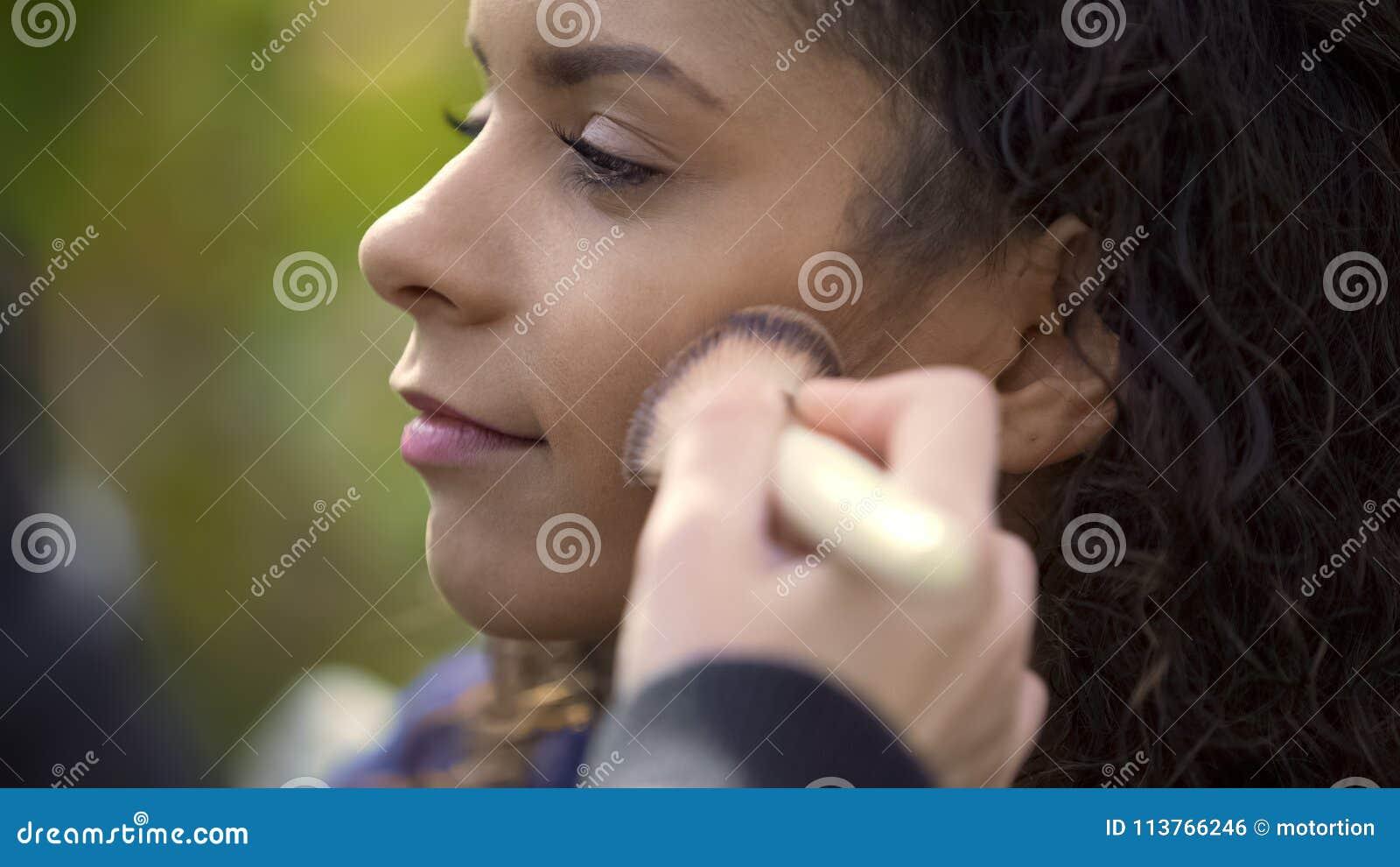 Makeup artysta stosuje proszek z muśnięciem na policzkach dosyć mieszany rasa model